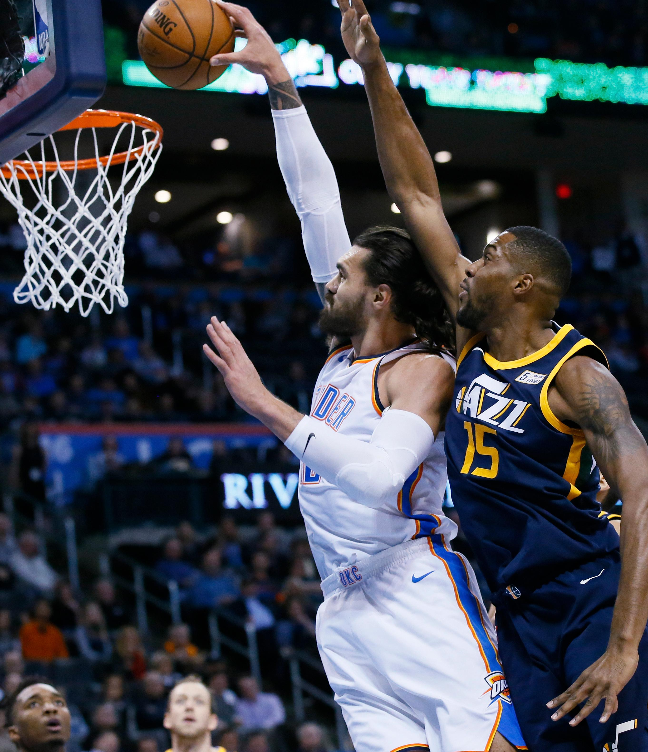 Oklahoma City Thunder center Steven Adams, left, shoots in front of Utah Jazz forward Derrick Favors (15) in the first quarter of an NBA basketball game in Oklahoma City, Tuesday, Dec. 5, 2017. (AP Photo/Sue Ogrocki)