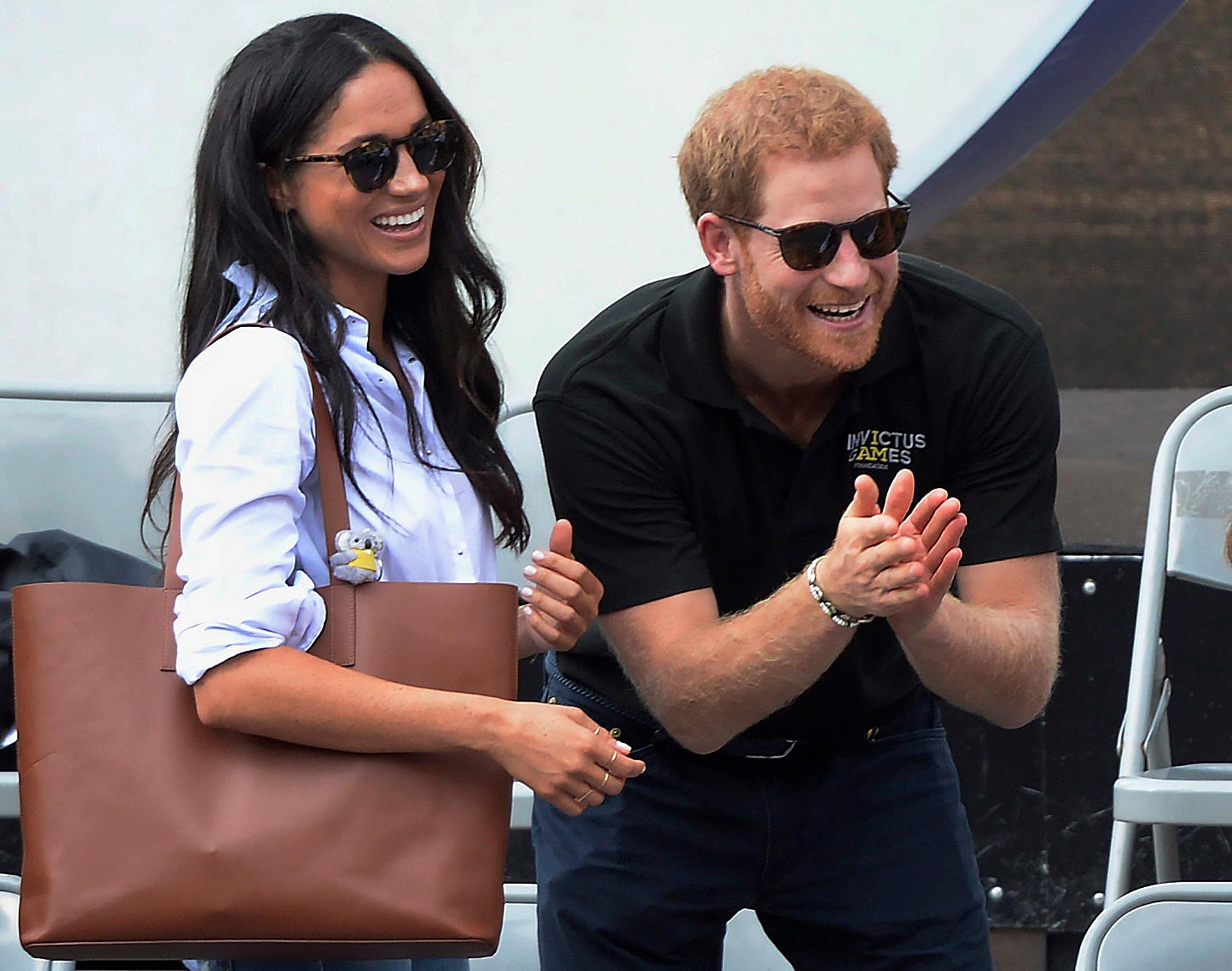 FILE - In this Monday, Sept. 25, 2017 file photo, Britain's Prince Harry and his girlfriend Meghan Markle attend the wheelchair tennis competition during the Invictus Games in Toronto. Palace officials announced Monday Nov. 27, 2017, Prince Harry and Meghan Markle are engaged, and will marry in the spring. (Nathan Denette/The Canadian Press via AP, File)
