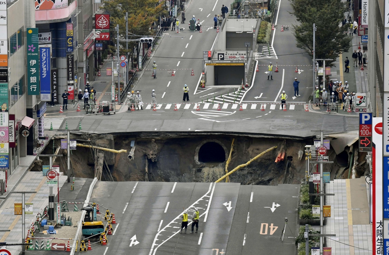 A massive shinkhole is created in the middle of the business district in Fukuoka, southern Japan Tuesday, Nov. 8, 2016. Parts of a main street have collapsed in the city, creating a huge sinkhole and cutting off power, water and gas supplies to parts of the city. Authorities said no injuries were reported from Tuesday's pre-sunrise collapse in downtown Fukuoka. (Sadayuki Goto/Kyodo News via AP)