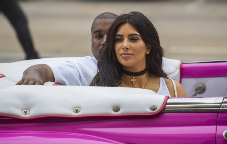 CORRRECTS NAME OF KANYE WEST - American reality-show star Kim Kardashian West and her husband, rap superstar,  Kanye West ride on a classic car in Havana, Cuba, Wednesday, May 4, 2016. West, Kardashian and members of her reality-show-star family have become the latest celebrities to visit Havana. They visited HavanaÂ?s Museum of Rum Wednesday, stepping out of a hot-pink antique American convertible as they snapped selfies and were recorded by a television crew following them around. (AP Photo/Desmond Boylan)