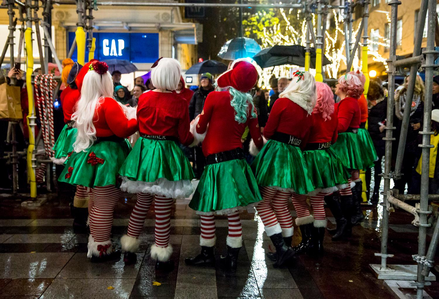 Thousands of people attended the annual Great Figgy Pudding Caroling Competition in downtown Seattle and Westlake Center on Friday night, December 1. The event raises funds for the Pike Market Senior Center and Food Bank which offers free meals, groceries, one-one-one counseling and other services to low-income and homeless neighbors in need. Dozens of caroling teams sing their hearts out on street corners in and around Westlake Center, and the top teams then compete in a sing-off on the Figgy Main Stage. (Sy Bean / Seattle Refined)
