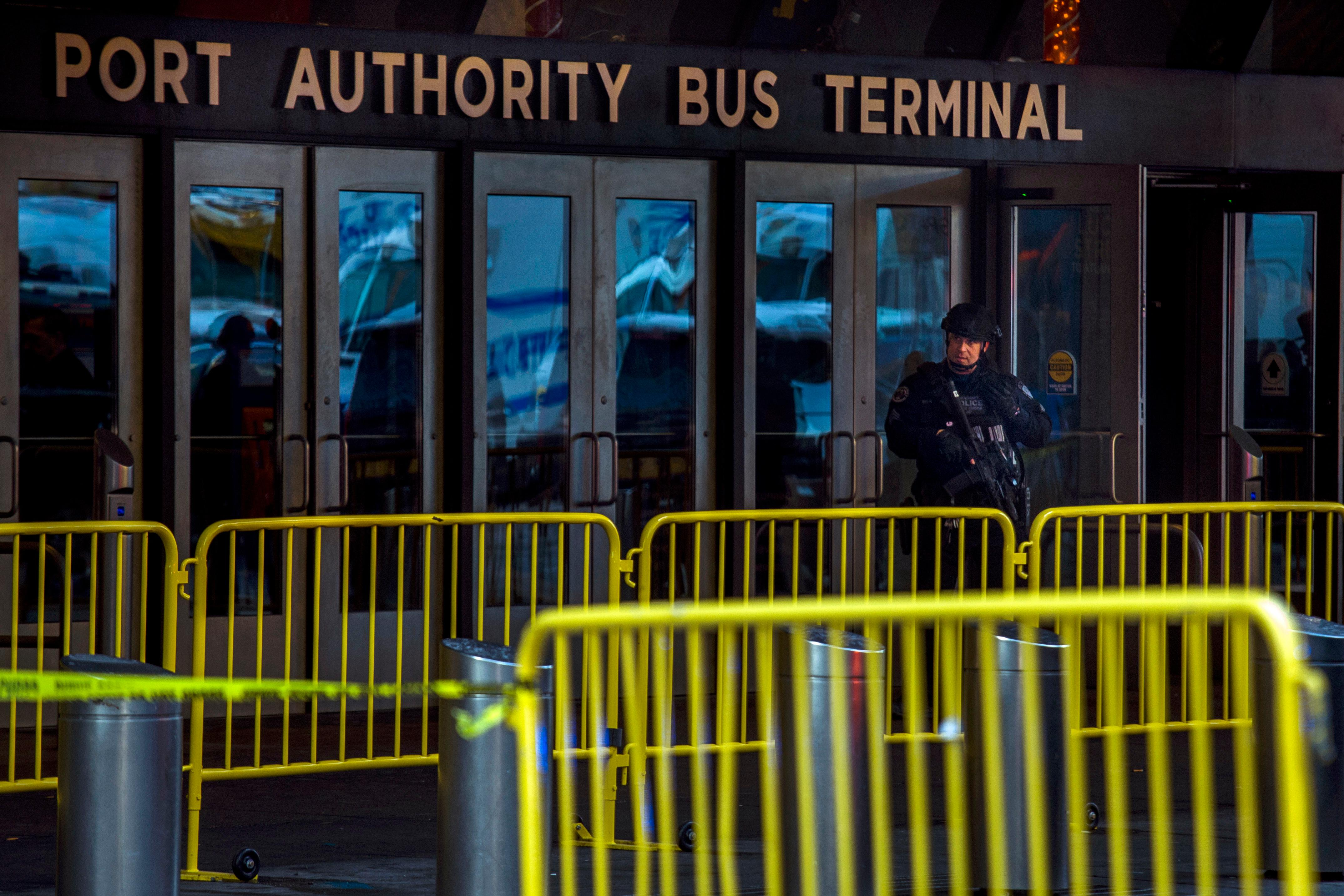 A police officer stands guard in front of Port Authority Bus Terminal as law enforcement respond to a report of an explosion near Times Square on Monday, Dec. 11, 2017, in New York. (AP Photo/Andres Kudacki)