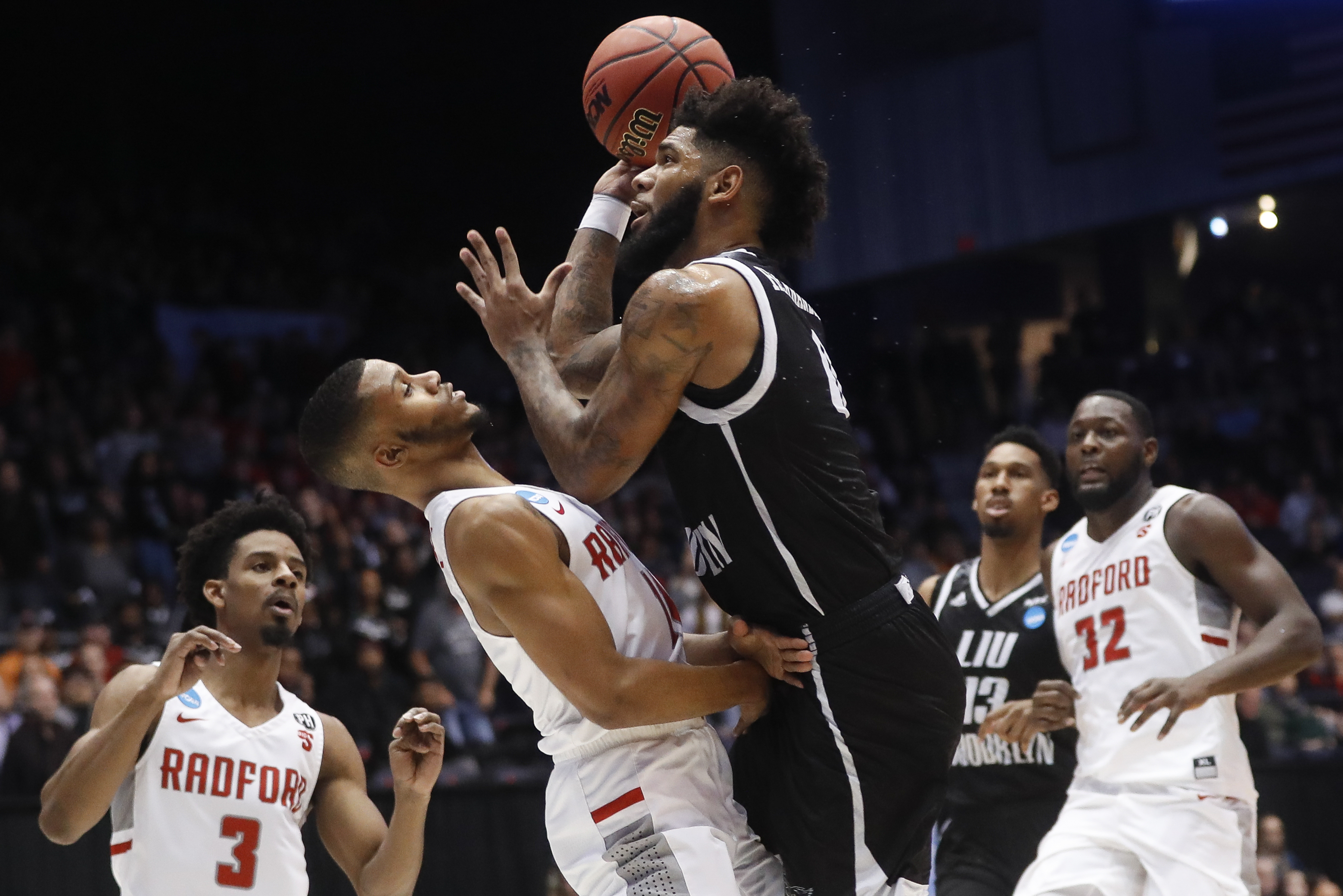 LIU Brooklyn's Joel Hernandez, center right, shoots against Radford's Travis Fields Jr. during the first half of a First Four game of the NCAA men's college basketball tournament, Tuesday, March 13, 2018, in Dayton, Ohio. (AP Photo/John Minchillo)