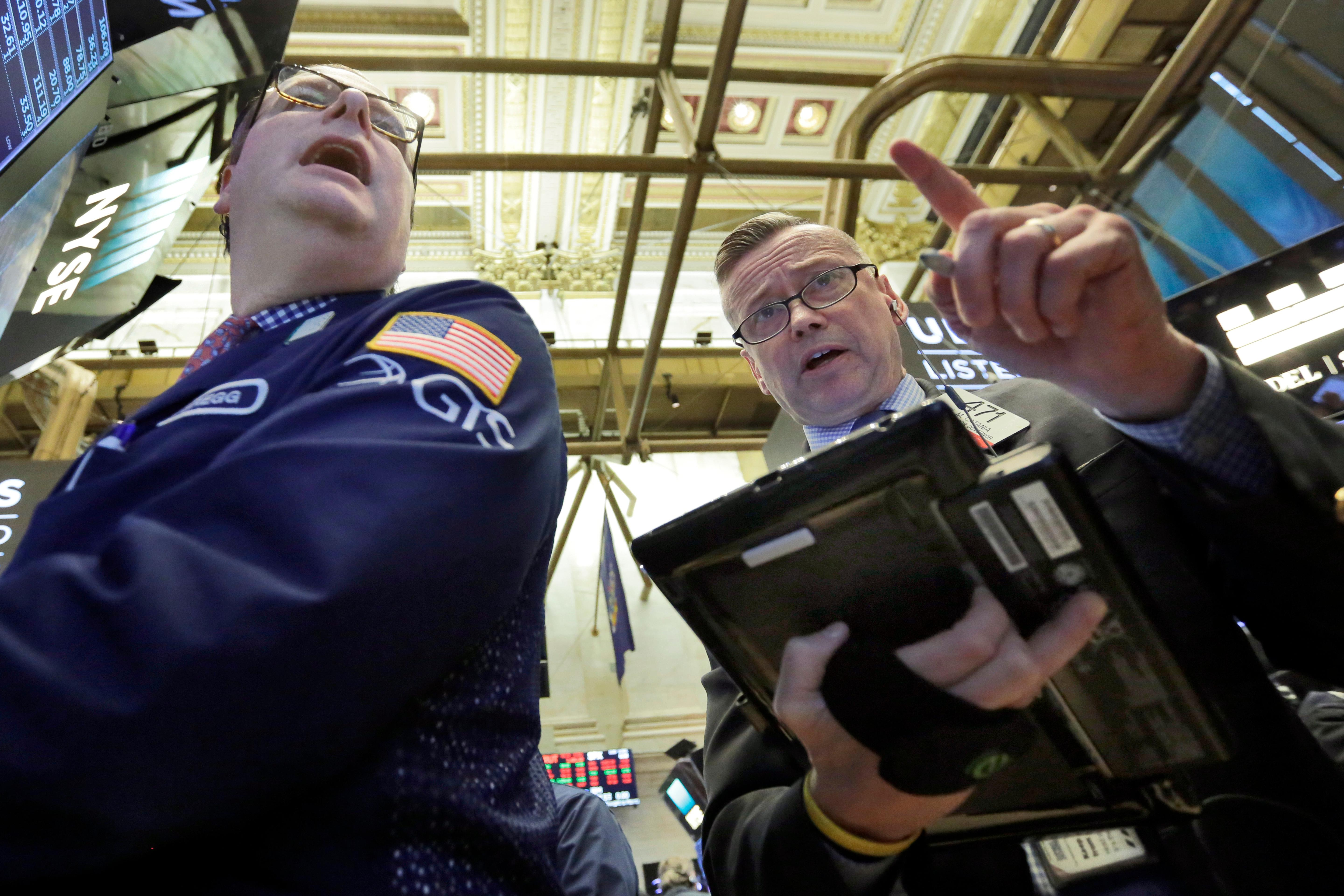 Specialist Gregg Maloney, left, and trader Neil Catania work on the floor of the New York Stock Exchange, Tuesday, Feb. 6, 2018. The Dow Jones industrial average fell as much as 500 points in early trading, bringing the index down 10 percent from the record high it reached on January 26. The DJIA quickly recovered much of that loss. (AP Photo/Richard Drew)