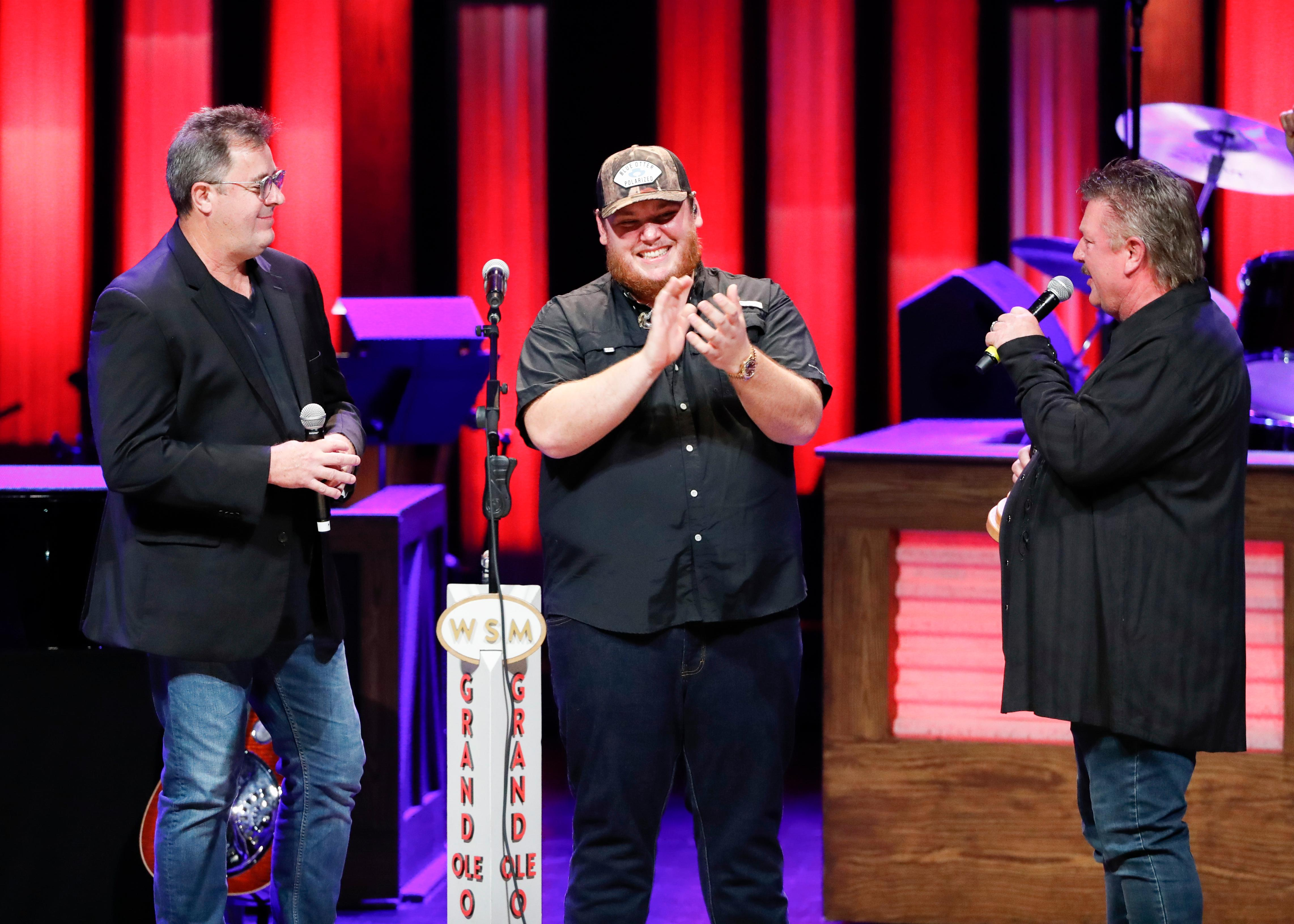 "Vince Gill, left, and Joe Diffie, right, welcome Luke Combs to the Grand Ole Opry at ""Luke Combs Joins the Grand Ole Opry Family,"" Tuesday, July 16, 2019, in Nashville, Tenn. (Photo by Al Wagner/Invision/AP)"