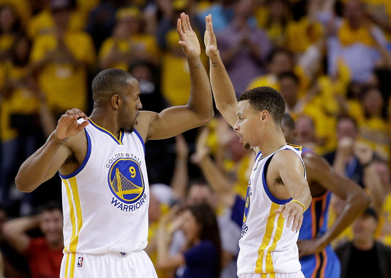 Golden State Warriors forward Andre Iguodala (9) and guard Stephen Curry (30) celebrate after scoring against the Oklahoma City Thunder during the first half of Game 2 of the NBA basketball Western Conference finals in Oakland, Calif., Wednesday, May 18, 2016. (AP Photo/Marcio Jose Sanchez)