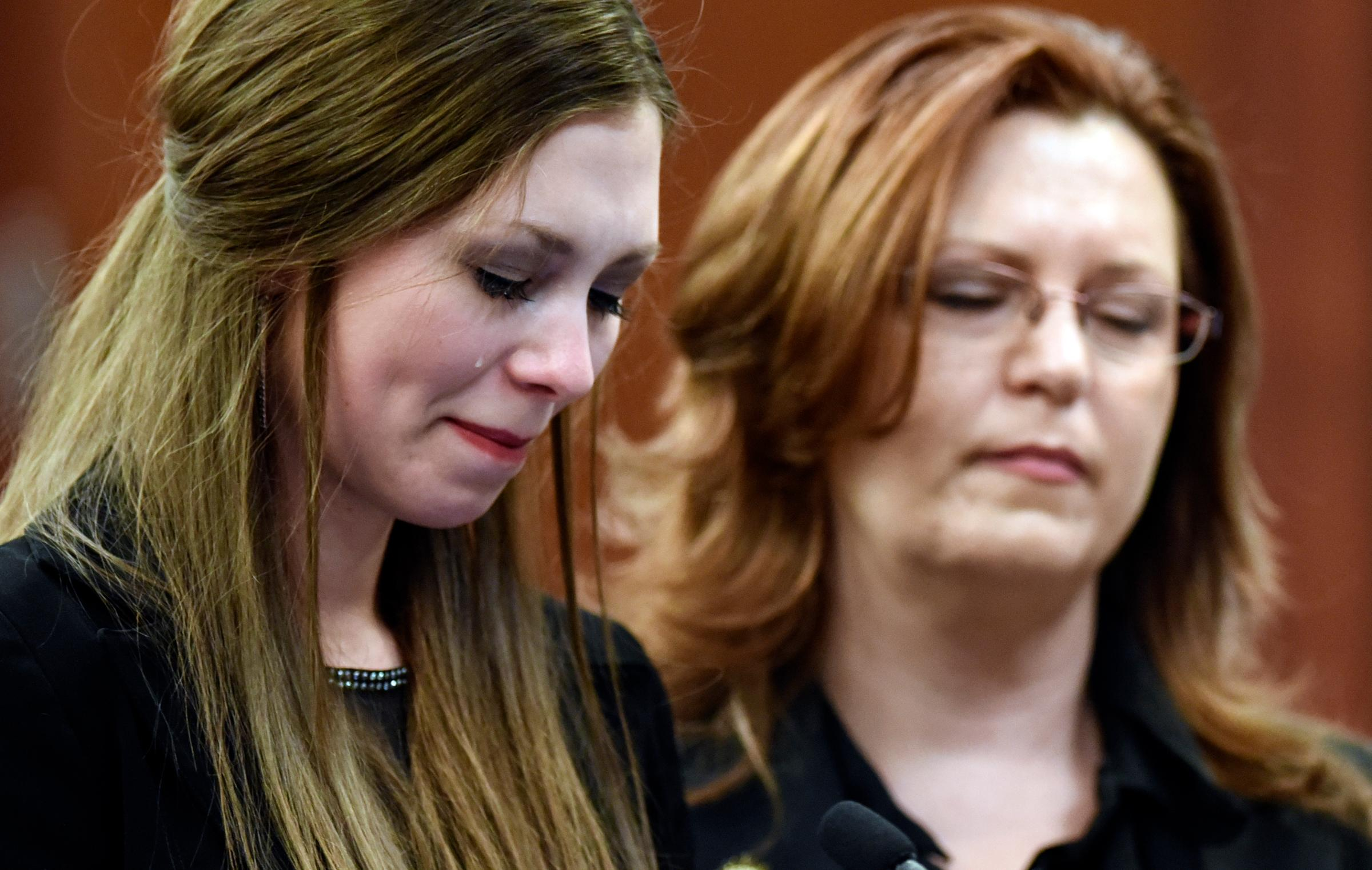 Dancer Jessica Smith, left, reacts while speaking Thursday, Jan. 18, 2018,in Lansing, Mich.,  during the third day of victim impact statements regarding former sports medicine doctor Larry Nassar, who pled guilty to seven counts of sexual assault in Ingham County, and three in Eaton County. Next to her is her mother Kimberly.  (Matthew Dae Smith /Lansing State Journal via AP)