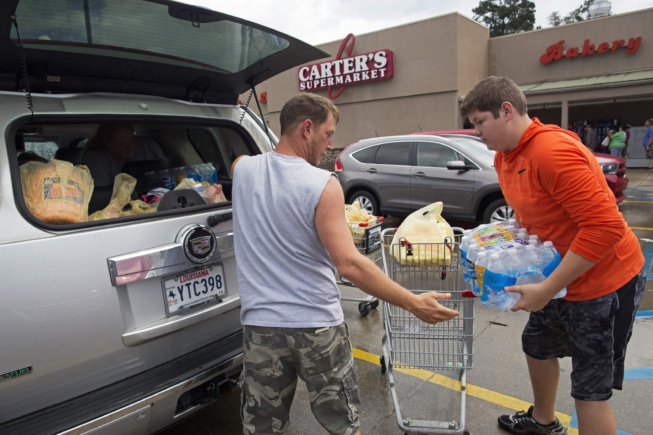 Eli Turnage, 14, right, helps Thomas Creel load his groceries at the Carter's Supermarket in Livingston, La., Monday, Aug. 15, 2016. The store opened for the first time today since flooding started in the region. Turnage is volunteering at the supermarket to keep himself busy after his home was destroyed from the flooding. The Creel family was stocking up before returning to their flood damaged home. (AP Photo/Max Becherer)