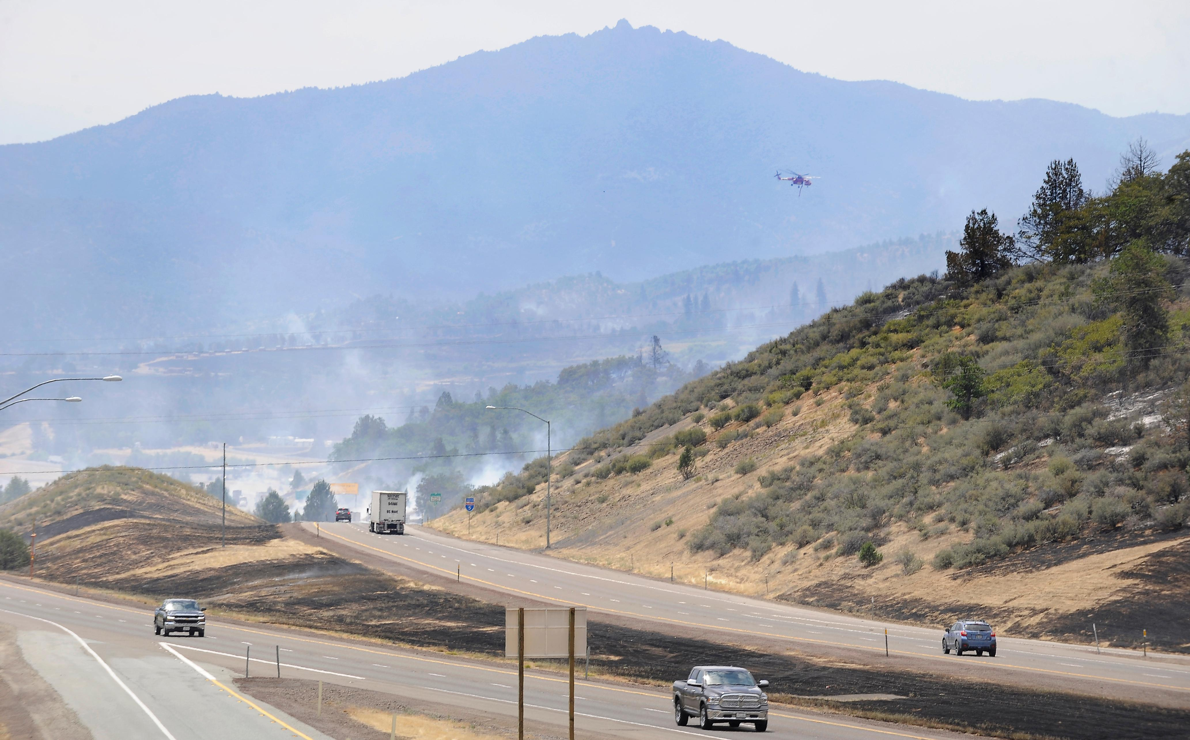 Andy Atkinson / Mail Tribune<br>A helicopter heads up to the mountainside near I-5 to fight flames burning just miles south of the Oregon-California border Friday afternoon.