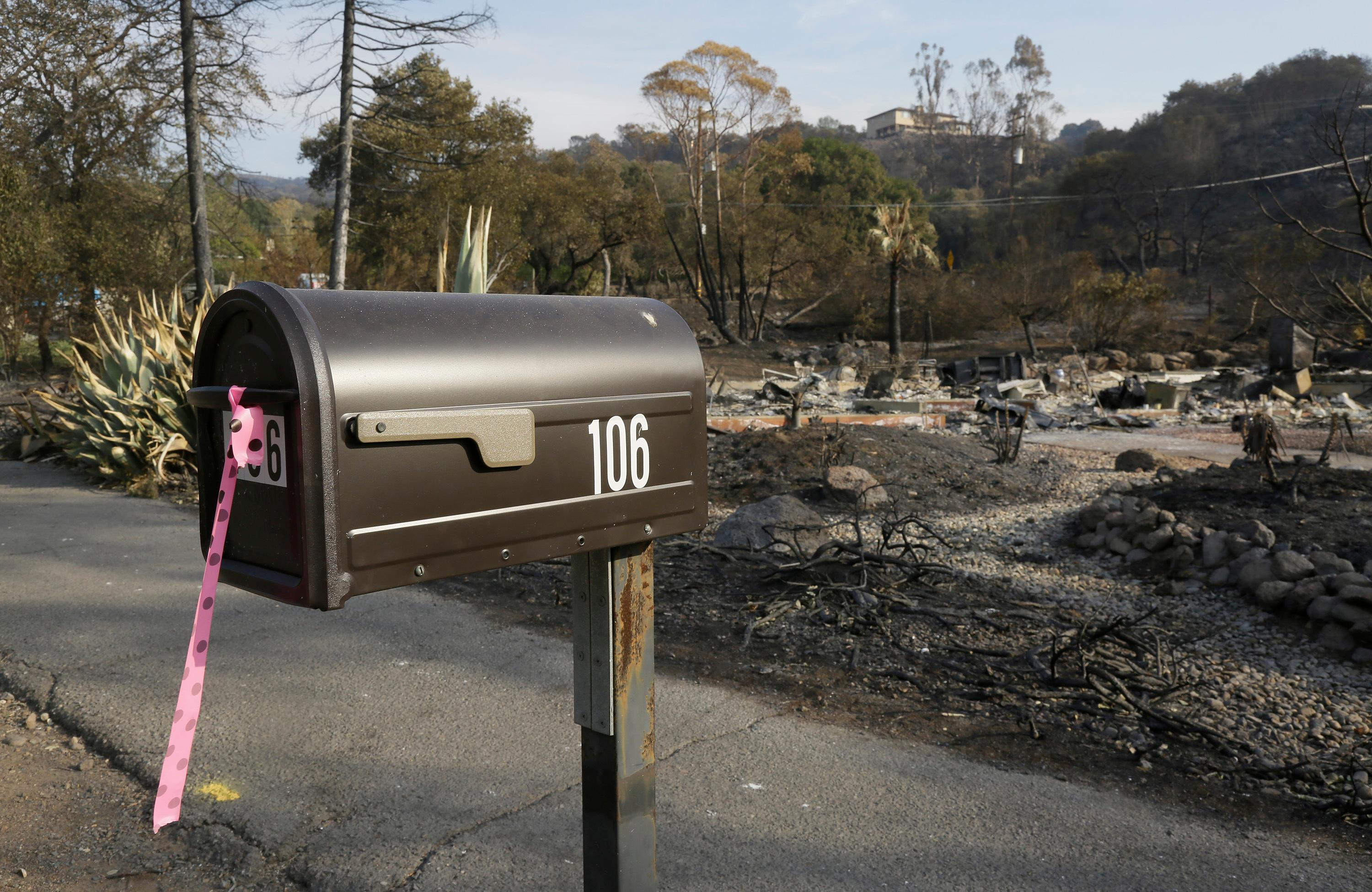 A mailbox stands Monday, Oct. 16, 2017, outside the remains of the home where Sara and Charles Rippey died a week ago in a fast-moving wildfire in Napa, Calif. The couple, 98 and 100 years old, had been married over 75 years. With the winds dying down, fire crews gained ground as they battled wildfires that have devastated California wine country and other parts of the state over the past week, and thousands of people got the all-clear to return home. (AP Photo/Eric Risberg)