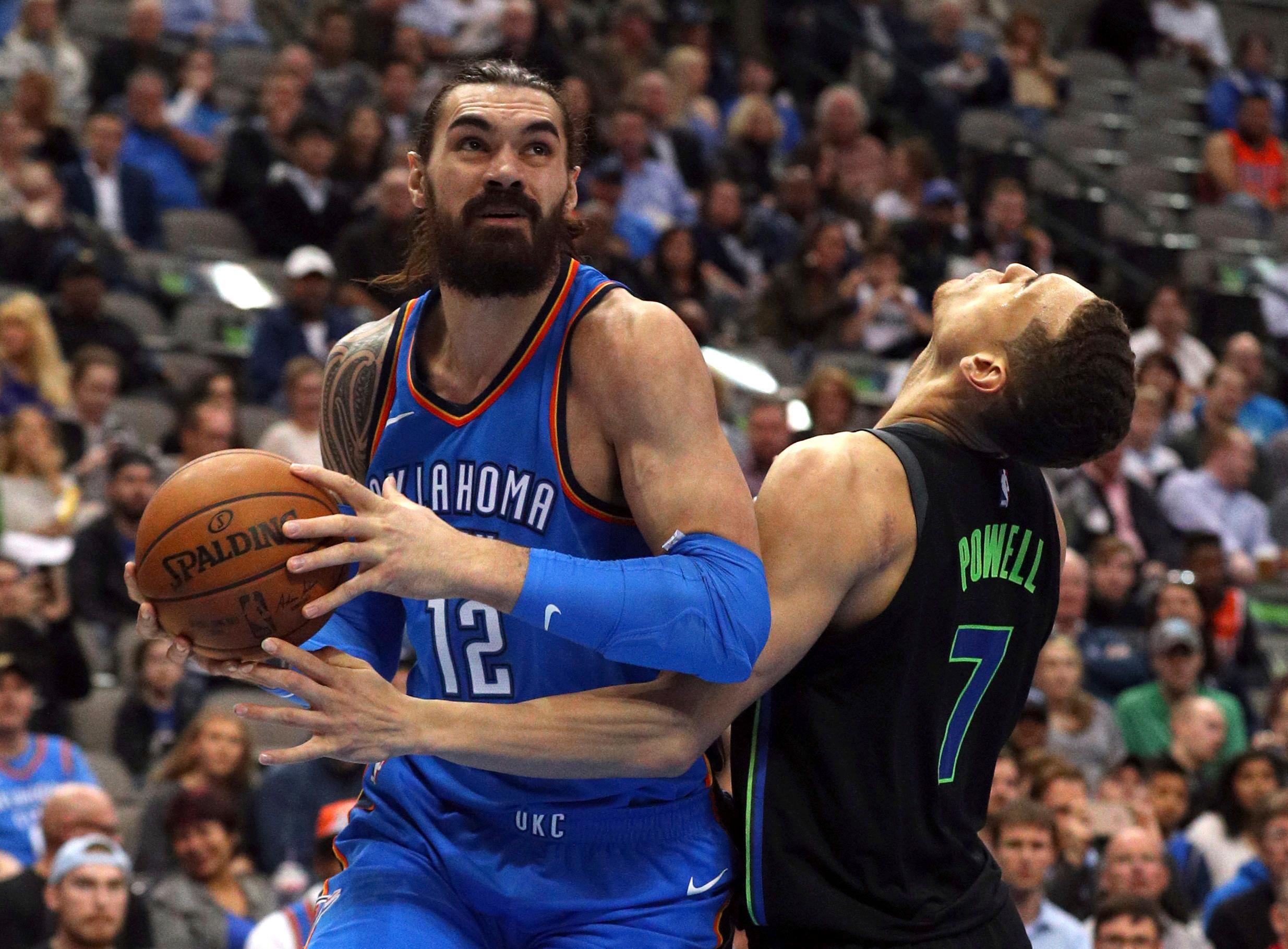 Oklahoma City Thunder center Steven Adams (12) gets fouled by Dallas Mavericks forward Dwight Powell (7) in the first half of an NBA basketball game Wednesday, Feb. 28, 2018 in Dallas. (AP Photo/ Richard W. Rodriguez)