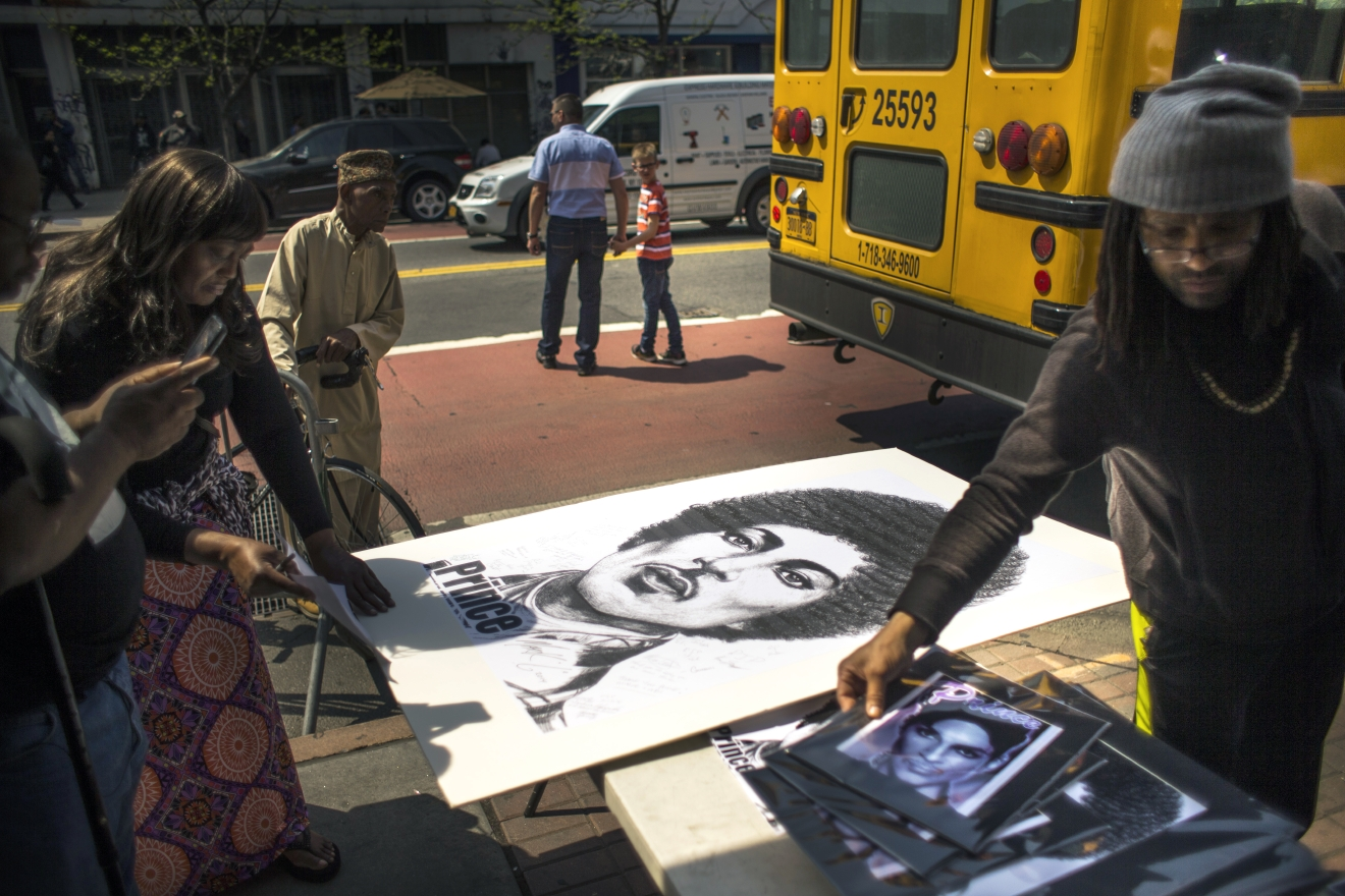People buy posters and pictures of Prince outside of the Apollo Theatre in New York, Friday, April 22, 2016. The pop star died Thursday at the age of 57. (AP Photo/Andres Kudacki)