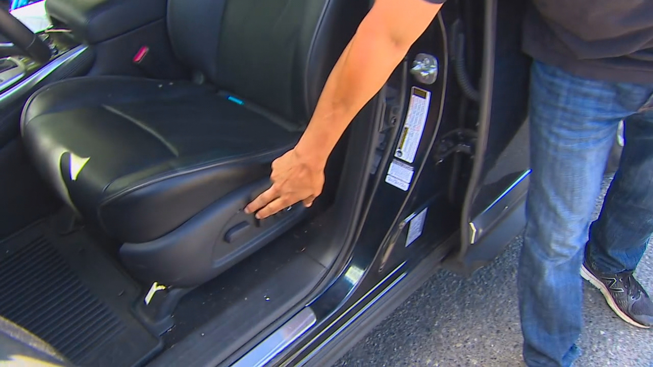 Mike Luiz shows where a bullet hole went through his driver's side door and into his seat. (KOMO Photo)