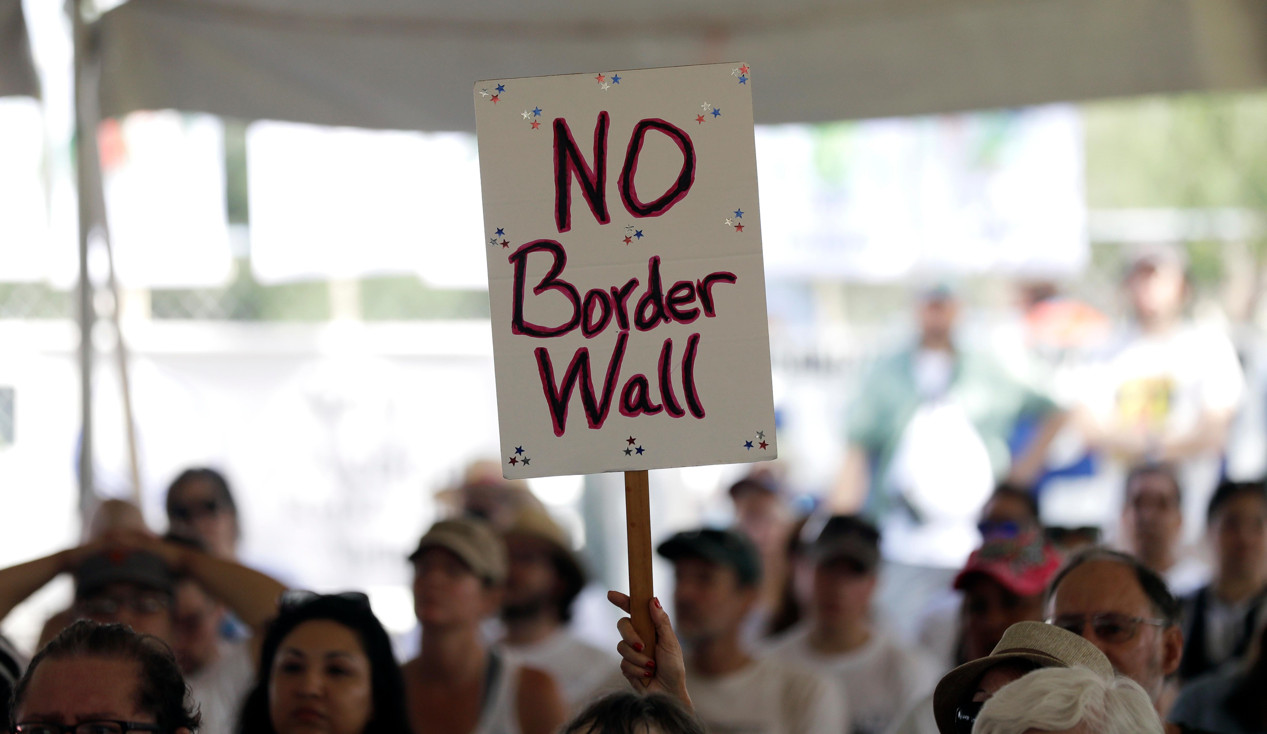 "A ""no border wall"" sign is held during a rally to oppose the wall the U.S. government wants to build on the river separating Texas and Mexico, Saturday, Aug. 12, 2017, in Mission, Texas. The area would be the target of new barrier construction under the Trump administration's current plan. (AP Photo/Eric Gay)"