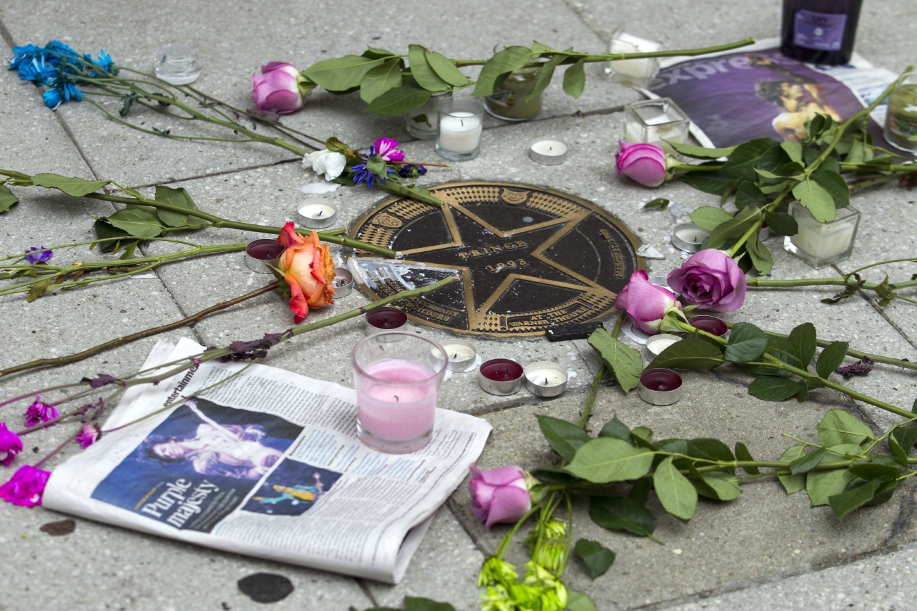 Flower are placed around musician Prince's star in a makeshift memorial on the sidewalk outside of the Warner Theatre in Washington, Friday, April 22, 2016. The pop star died Thursday at age 57.  (AP Photo/Jose Luis Magana)