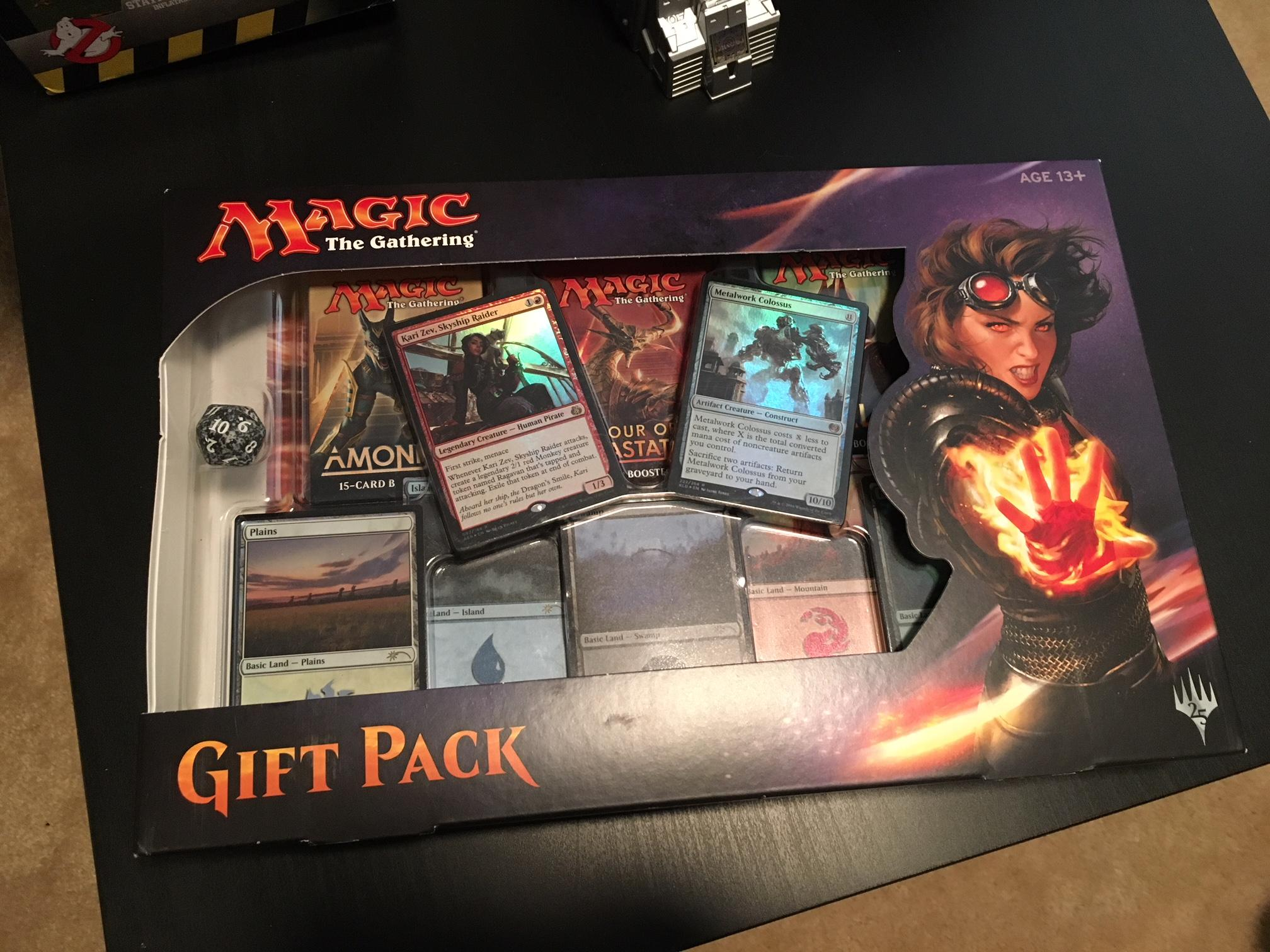 "This Magic: The Gathering gift pack includes 5 premium basic lands by artist Mark Poole, known as the ""Shooting Star Lands,"" 2 premium creature cards--Metalwork Colossus and Kari Zev, Skyship Raider--3 booster packs including Ixalan, Hour of Devastation, and Amonkhet, Spindown life counter, and an exclusive mini-poster (Photo: SBG)"