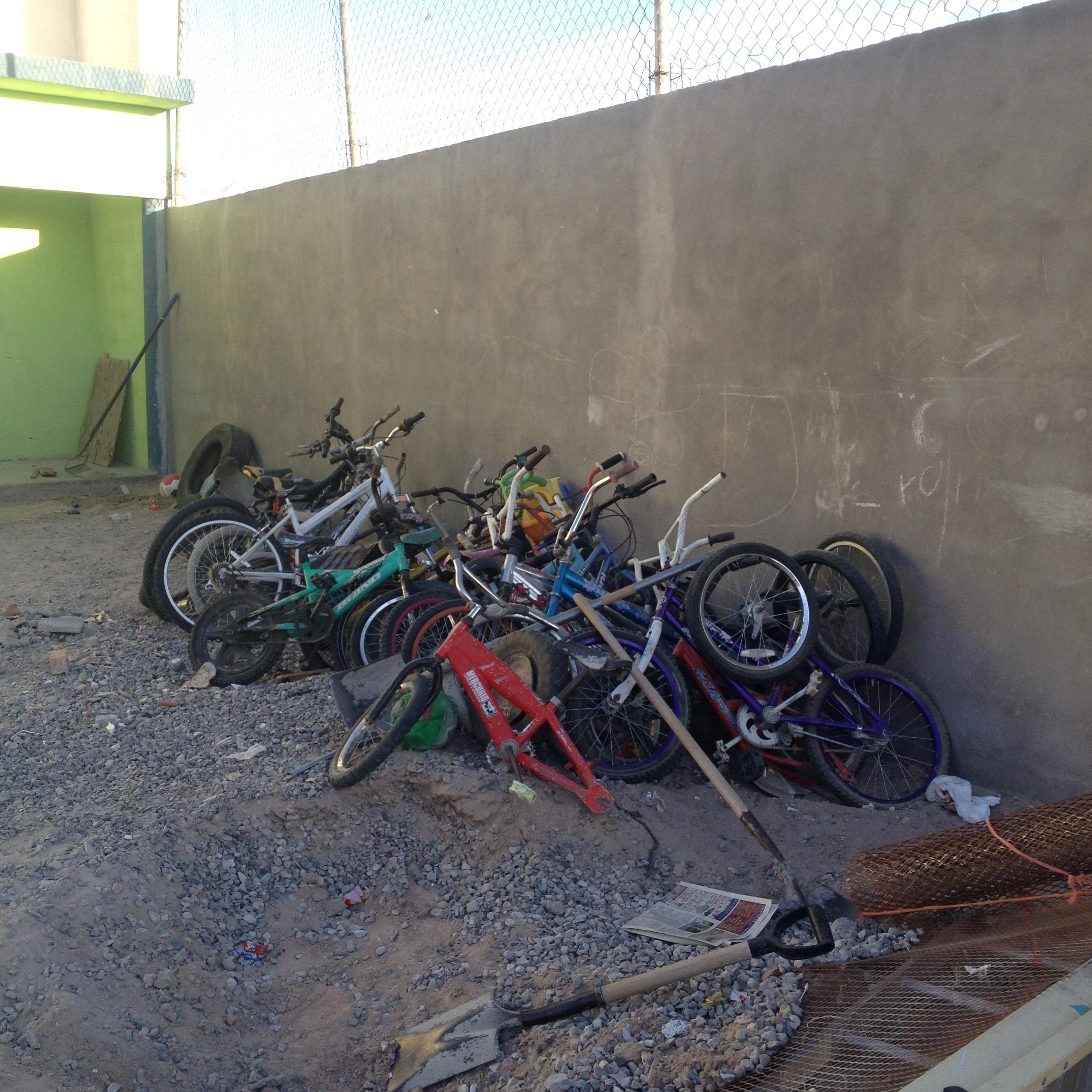 Bicycles neatly piled outside the boy's bedrooms building.
