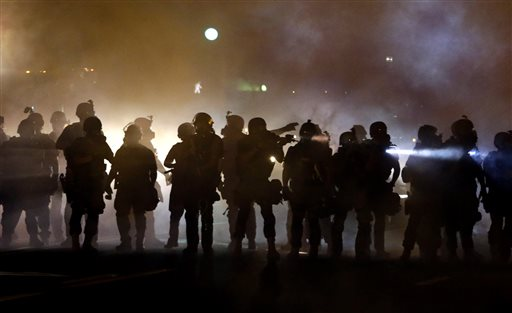 Police walk through a cloud of smoke as they clash with protesters Wednesday, in Ferguson, Mo.