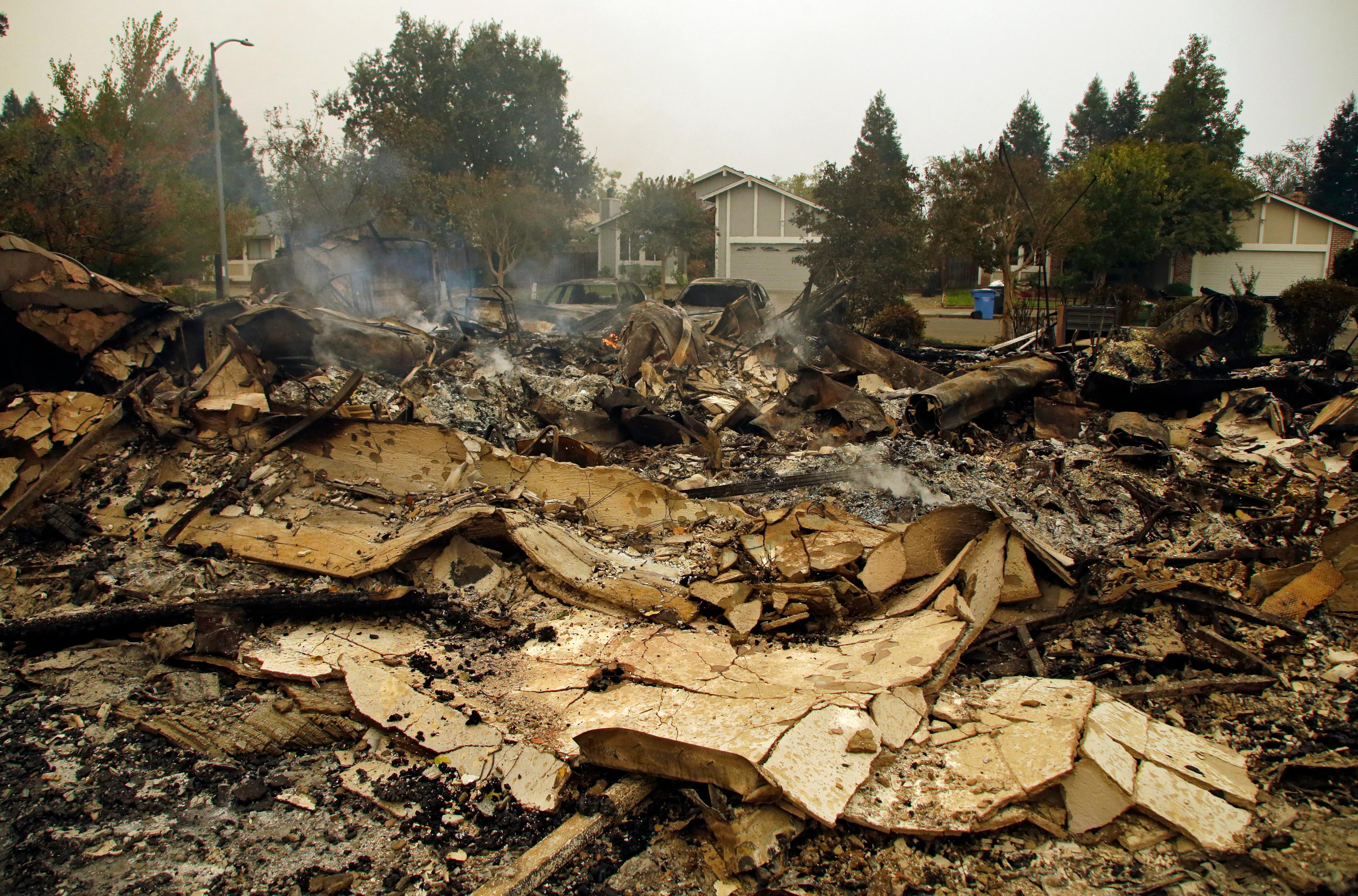 Smoke raises from the remains of homes across the street from houses unscathed on Tuesday, Oct. 10, 2017, in the Coffey Park area of Santa Rosa, Calif. An onslaught of wildfires across a wide swath of Northern California broke out almost simultaneously then grew exponentially, swallowing up properties from wineries to trailer parks and tearing through both tiny rural towns and urban subdivisions. (AP Photo/Ben Margot)