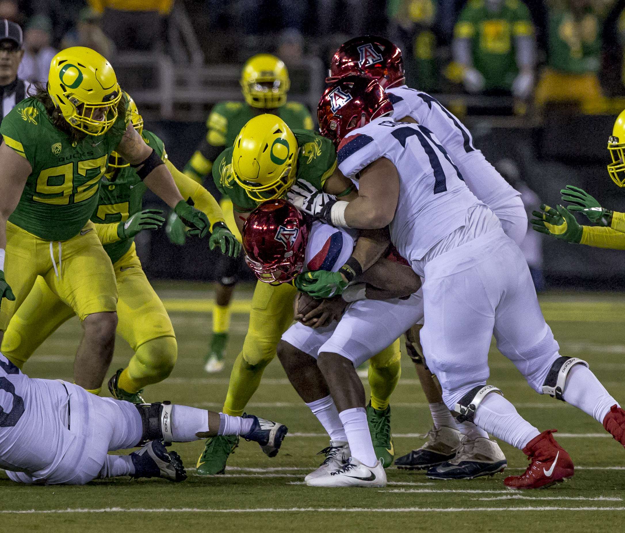 A pack of Oregon defenders take down an Arizona ball carrier. The Oregon Ducks defeated the Arizona Wildcats 48 to 28 during a chilly evening game at Autzen Stadium on November 18, 2017. Photo by Ben Lonergan, Oregon News Lab