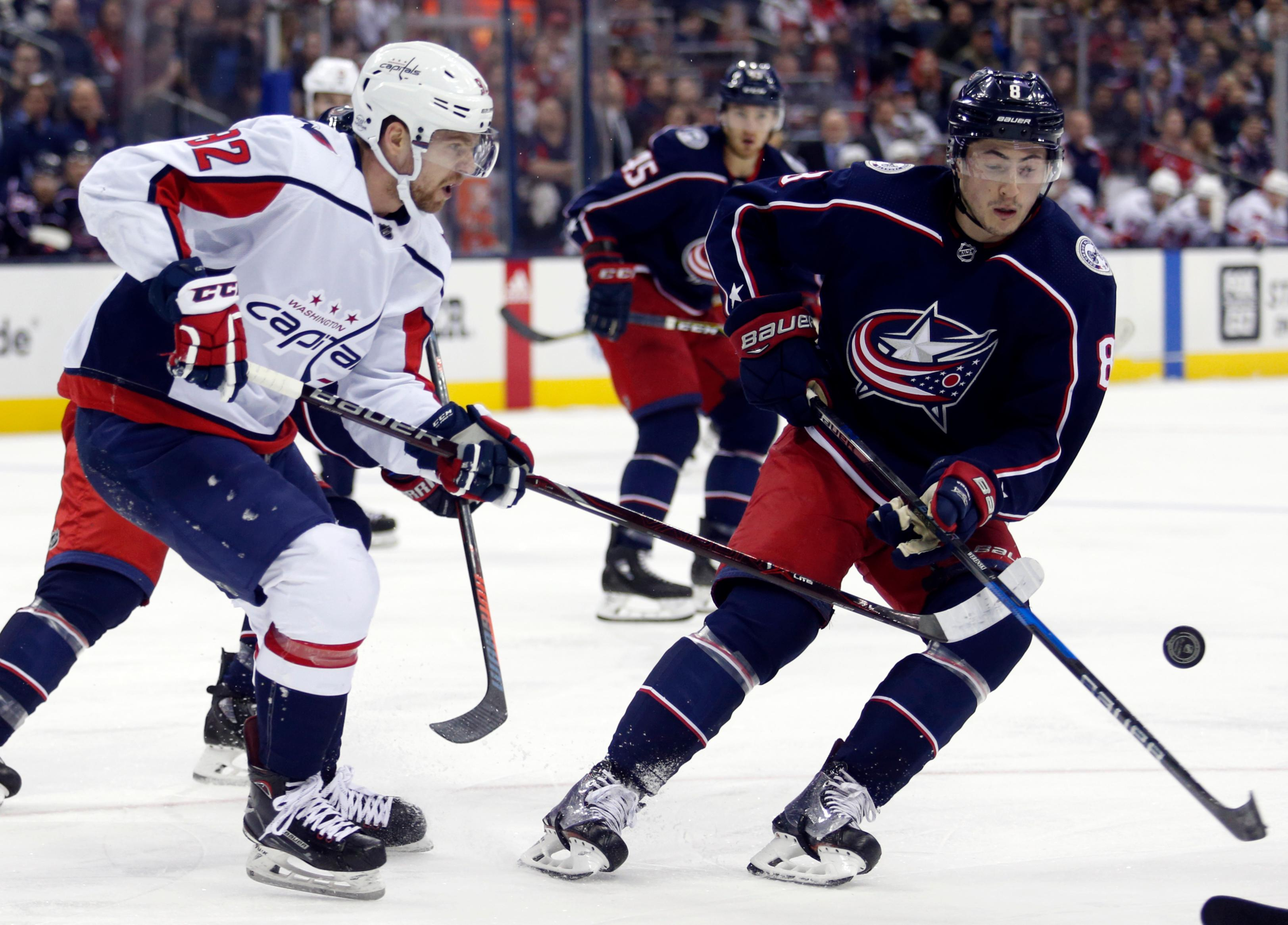 Washington Capitals forward Evgeny Kuznetsov, left, of Russia, passes the puck against Columbus Blue Jackets defenseman Zach Werenski during the first period of an NHL hockey game in Columbus, Ohio, Monday, Feb. 26, 2018. (AP Photo/Paul Vernon)