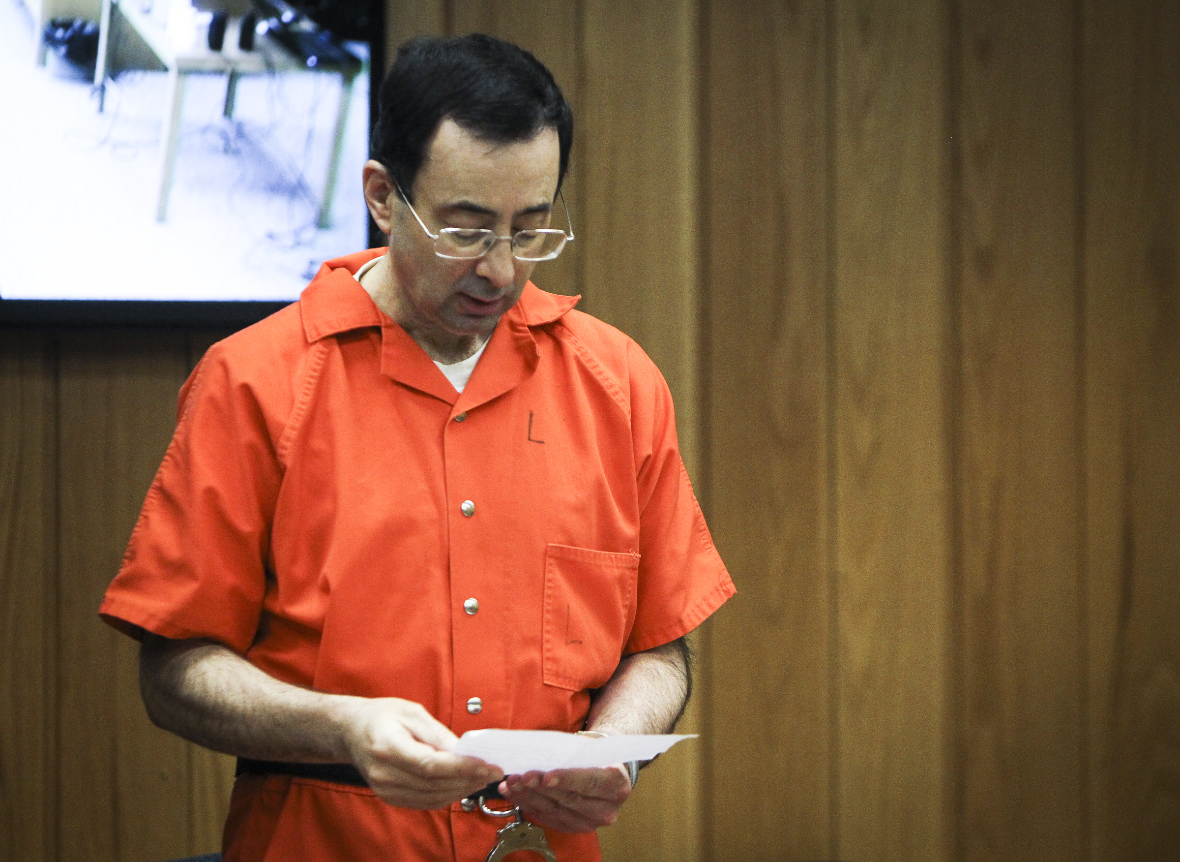 Larry Nassar reads a statement Monday, Feb. 5, 2018, during the third and final day of sentencing in Eaton County Court in Charlotte, Mich., where he will be sentenced on three counts of sexual assault. Nassar already has been sentenced to 40 to 175 years in prison in another county and is starting his time behind bars with a 60-year federal term for child pornography crimes. (Matthew Dae Smith/Lansing State Journal via AP)