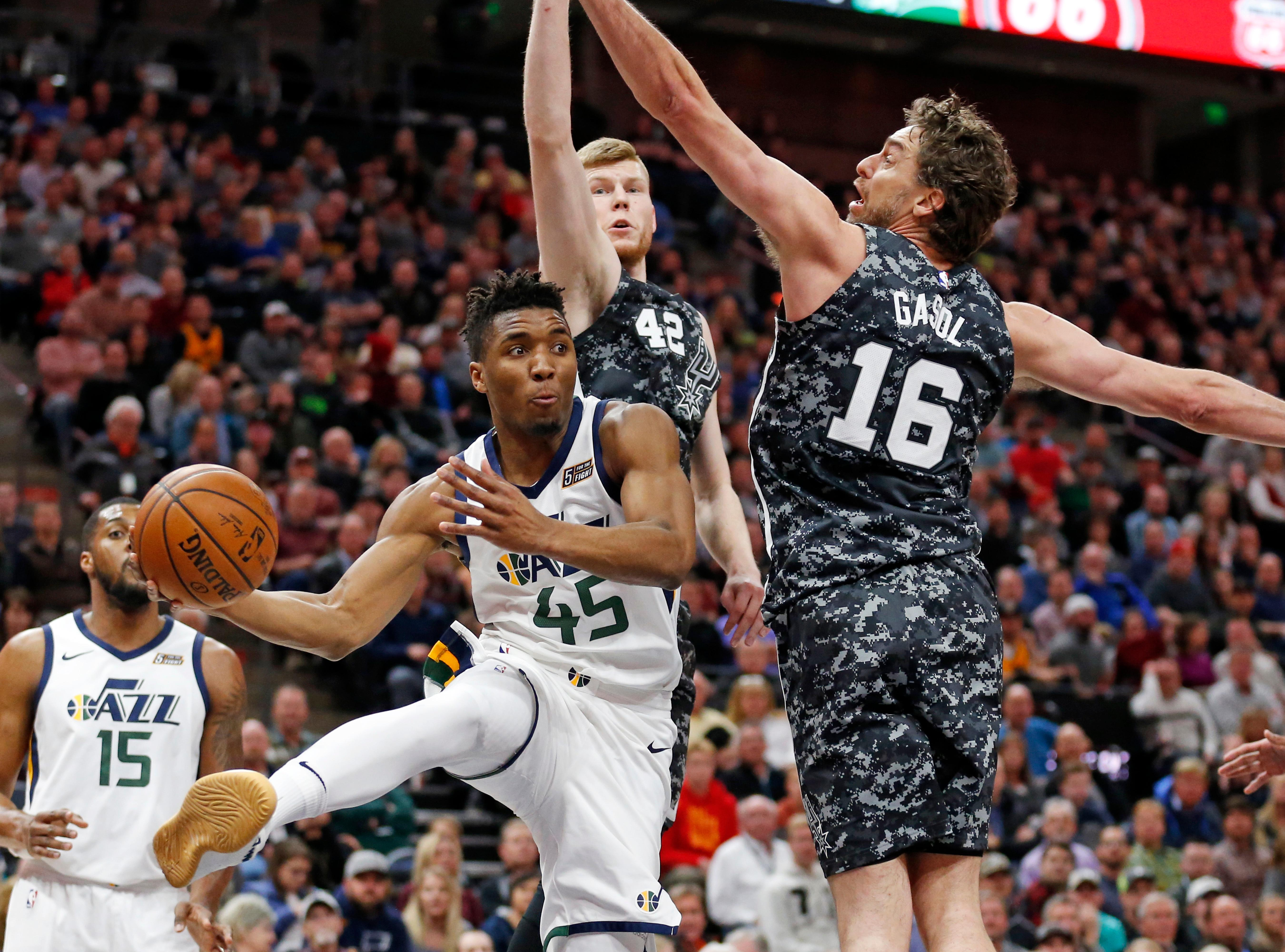 San Antonio Spurs' Davis Bertans (42) and Pau Gasol (16) defend against Utah Jazz guard Donovan Mitchell (45) in the first half of an NBA basketball game Monday, Feb. 12, 2018, in Salt Lake City. (AP Photo/Rick Bowmer)