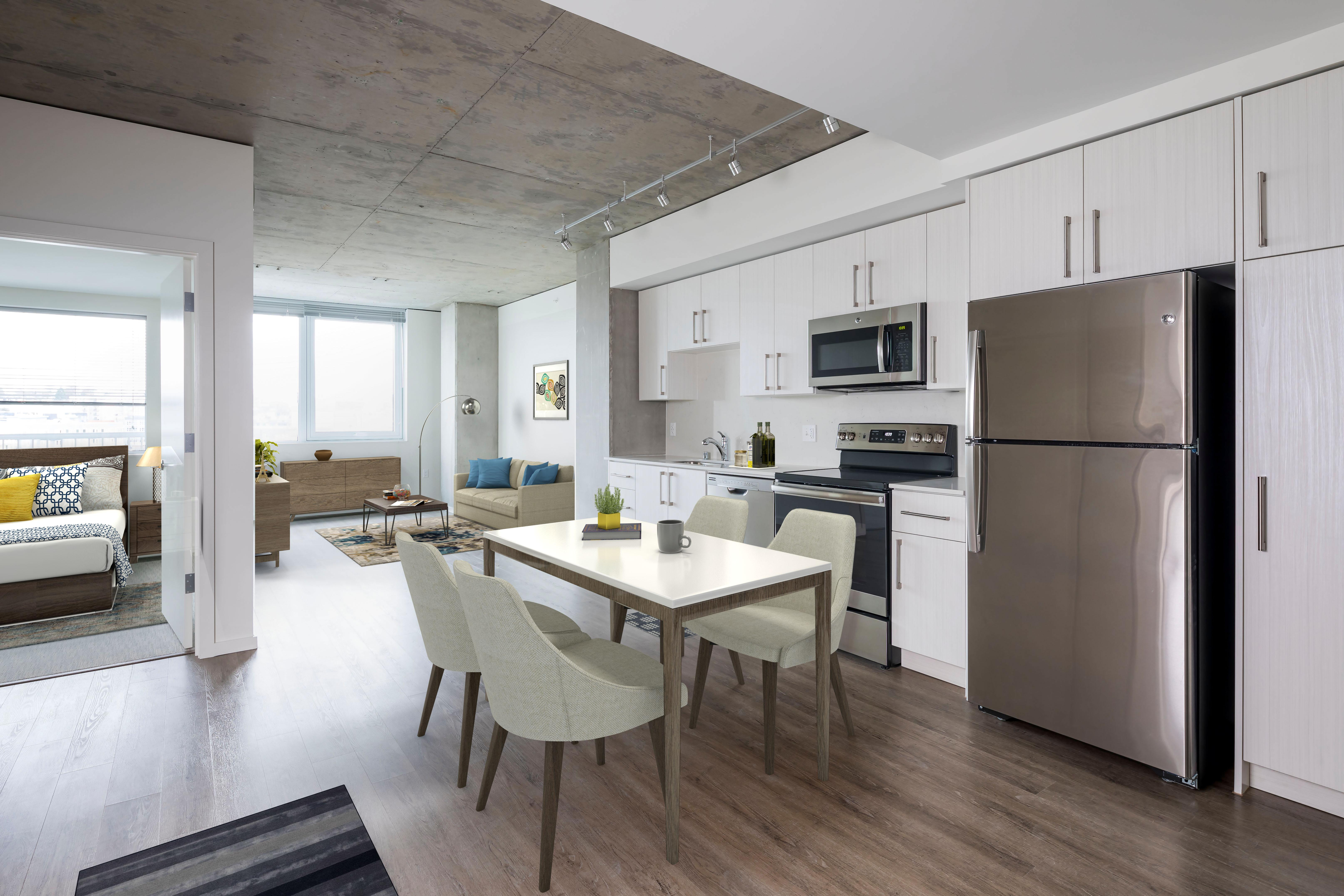 The Danforth kitchens feature cabinetry in warm wood or cool gray –a perfect complement to the Carrera style quartz countertops and backsplash.{ }
