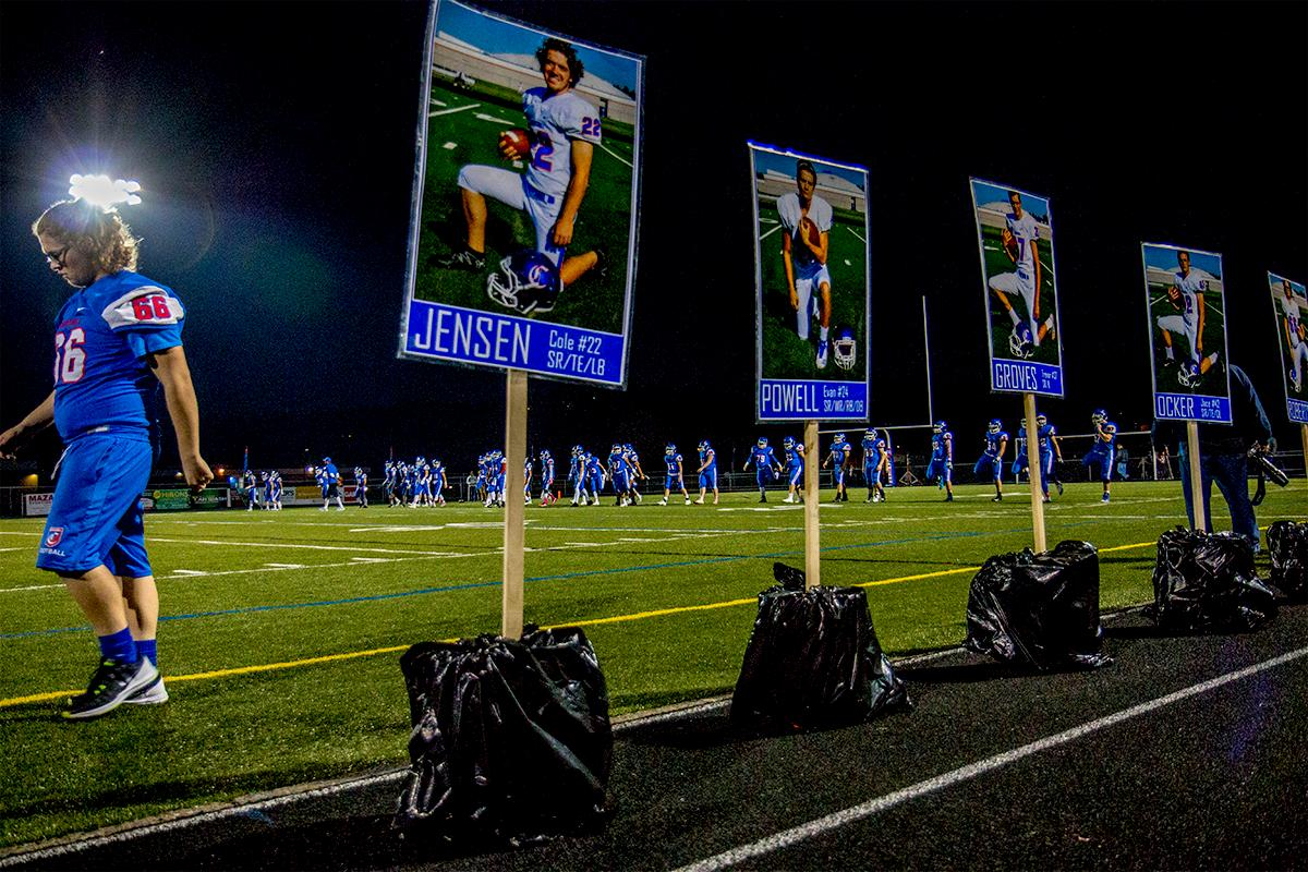 Senior photos sit next to the field for Churchill's homecoming game. Churchill defeated Crater 63-21 on Friday at their homecoming game. Churchill remains undefeated with a conference record of 9-0. Photo by Rhianna Gelhart, Oregon News Lab