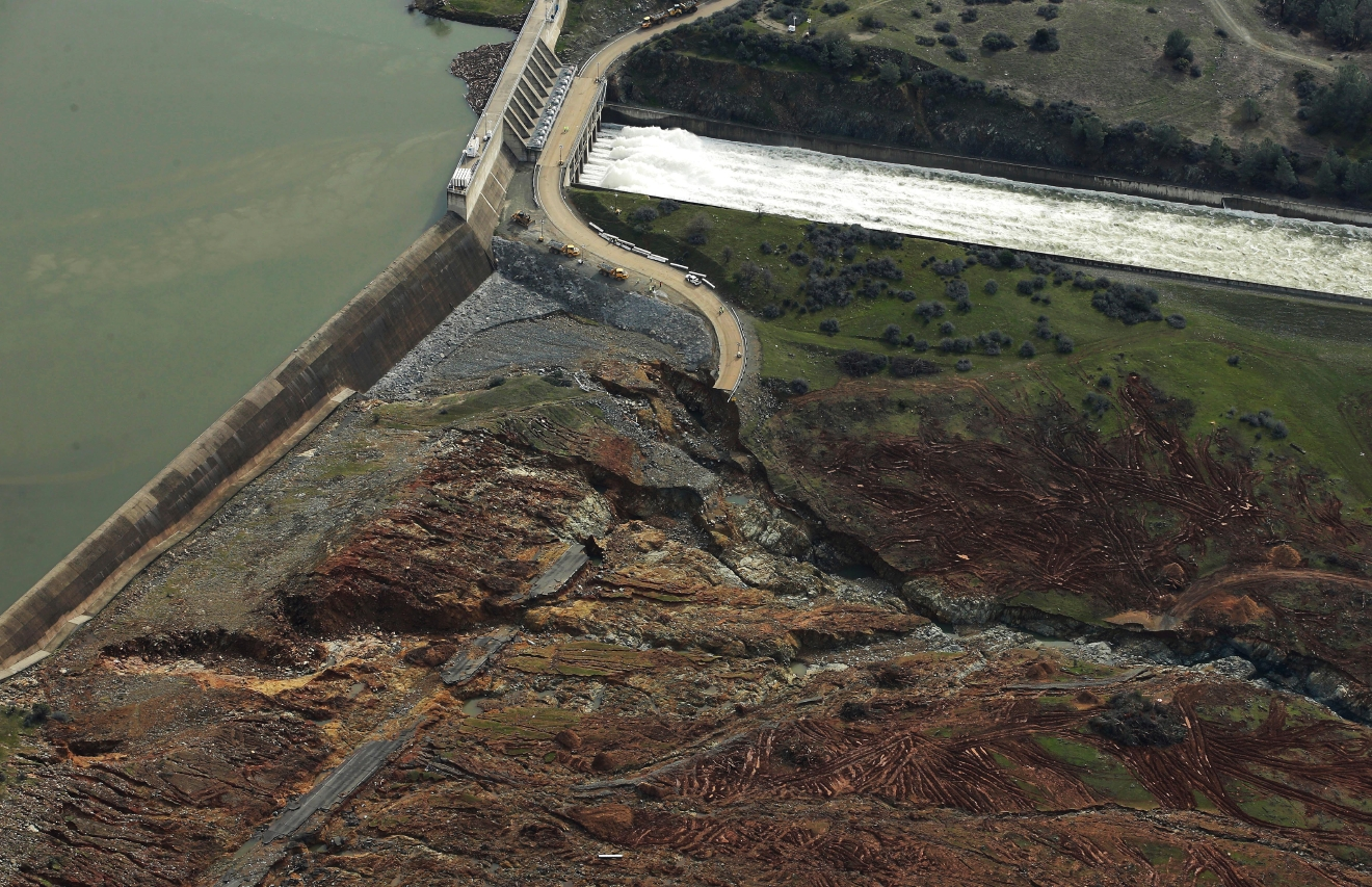 Erosion caused when overflow water cascaded down the emergency spillway is seen, bottom, as water continues to flow down the main spillway, top, of the Oroville Dam, Monday, Feb. 13, 2017, in Oroville, Calif. The water level dropped Monday at the nation's tallest dam, easing slightly the fears of a catastrophic spillway collapse that prompted authorities to order people to leave their homes downstream. (AP Photo/Rich Pedroncelli)