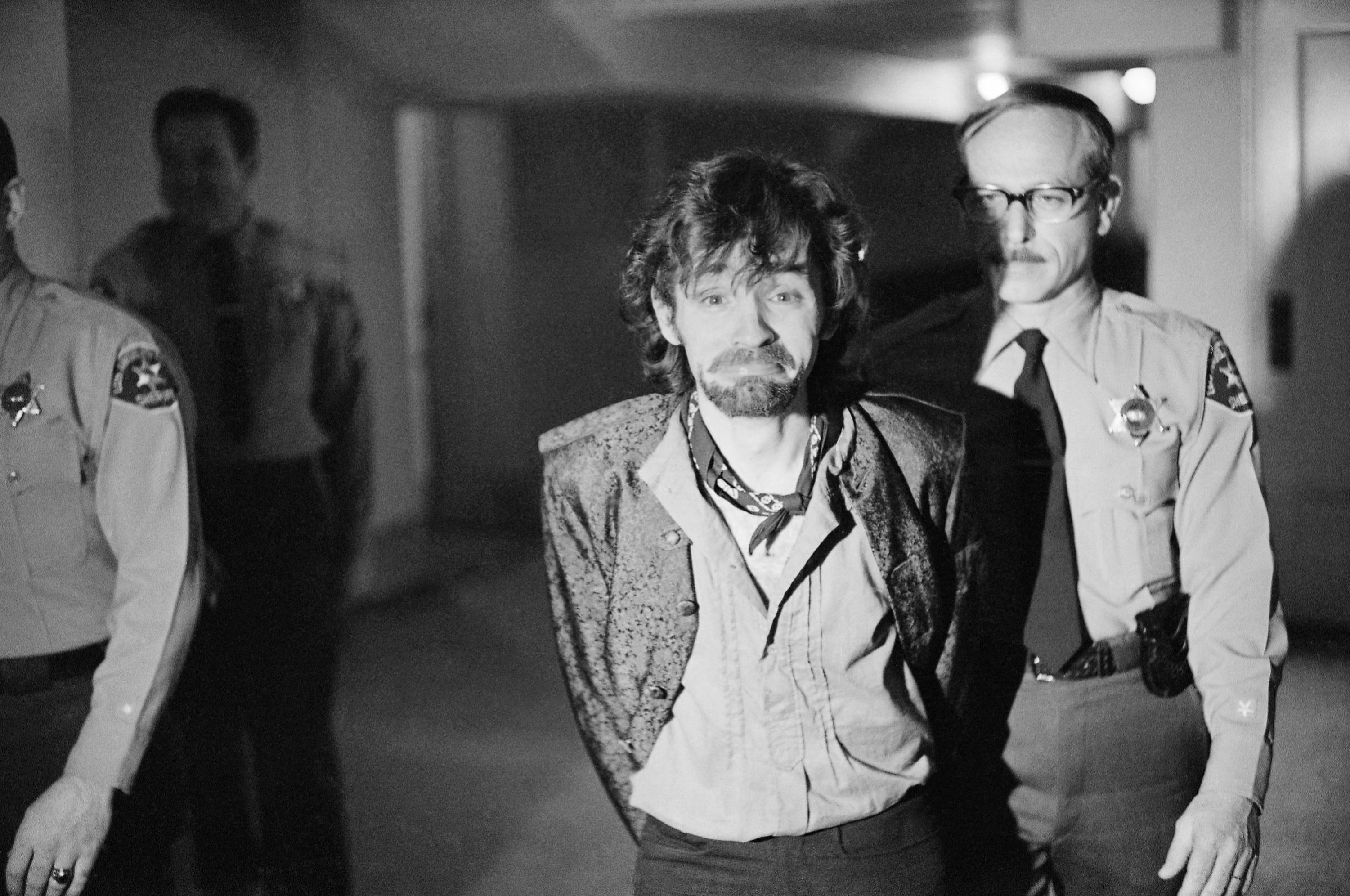 FILE - In this Dec. 21, 1970 file photo, Charles Manson reacts to photographers as he goes to lunch after an outbreak in court that resulted in his ejection, along with three female co-defendants, in the Sharon Tate murder trial.{&amp;nbsp;} (AP Photo/George Brich, File)<p></p>