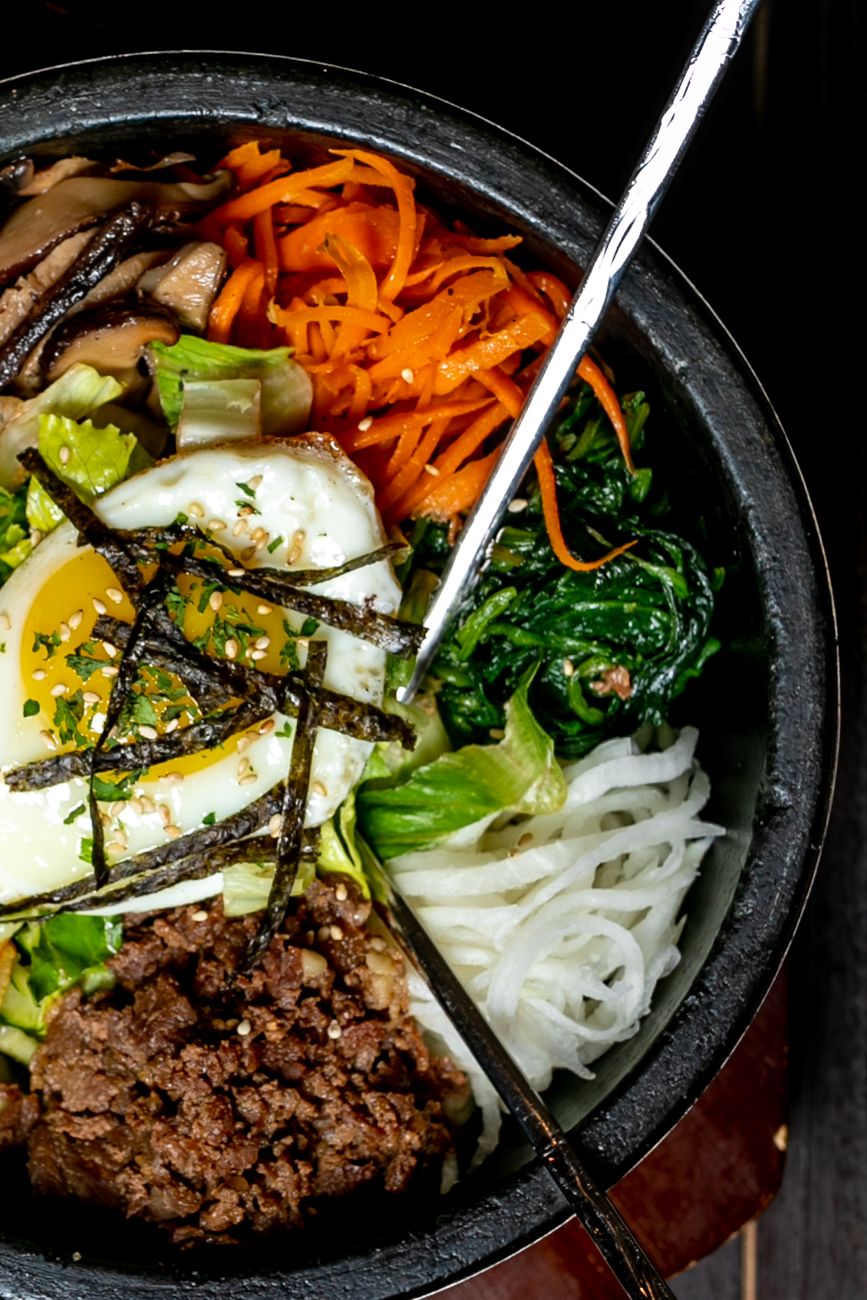<p>Dolsot Bibimbap: Steamed rice topped with spinach, radish, carrot, bean sprout, zucchini, mushroom, and your choice of meat (beef or chicken), or tofu, with a fried egg on top served in a sizzling hot stone bowl (homemade hot sauce on the side) / Image: Amy Elisabeth Spasoff // Published: 8.31.18</p>