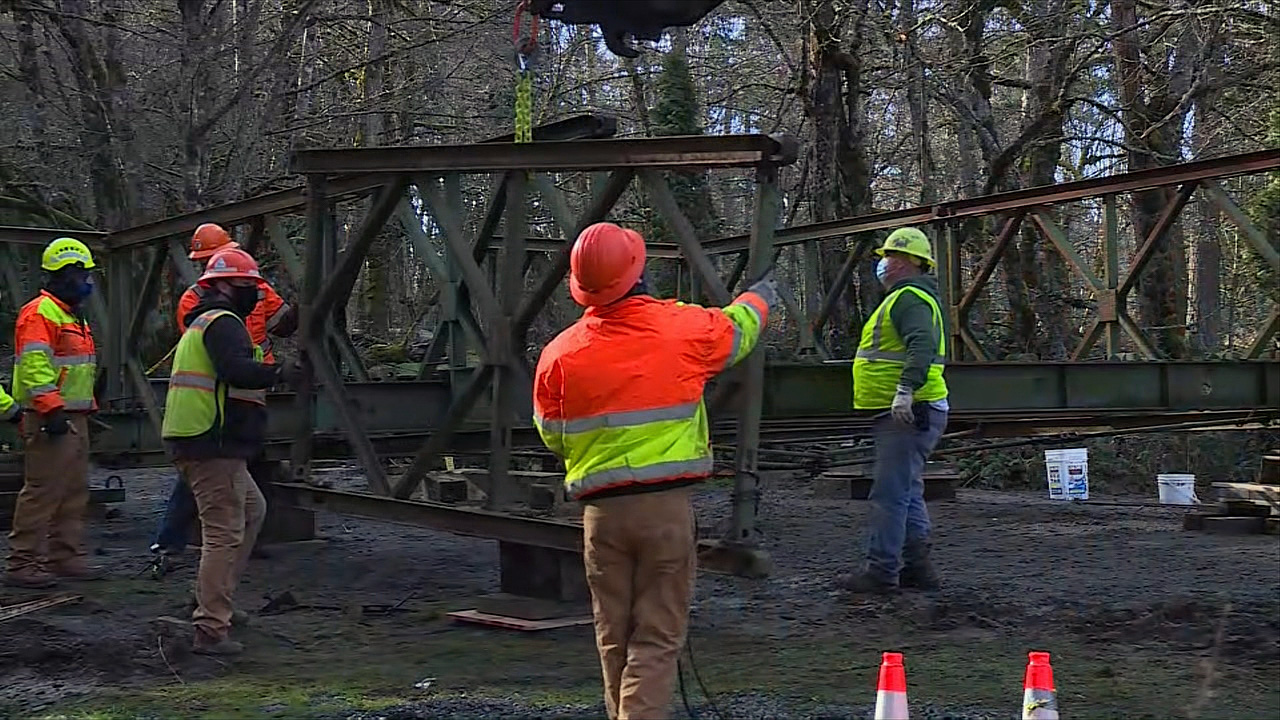 Crews work to install an emergency bridge Tuesday, Jan. 19, 2021 over a sinkhole that formed on Southeast Hideaway Court in Damascus after a recent rainstorm. (Pool)