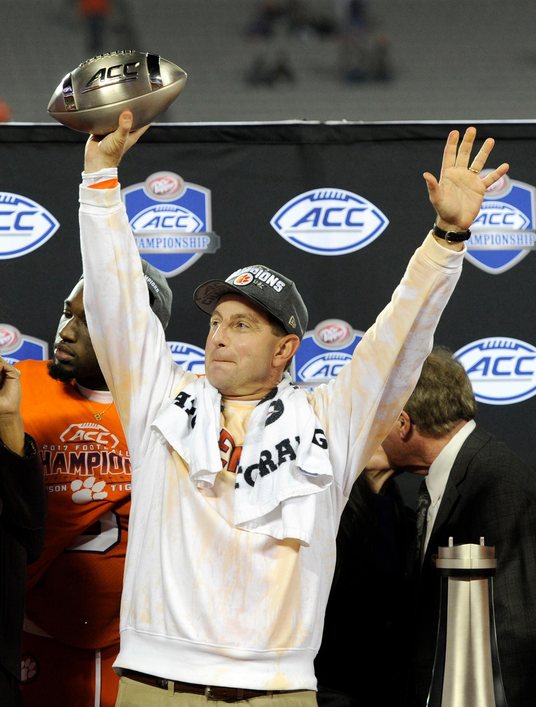 Clemson head coach Dabo Swinney celebrates with the trophy after Clemson's win over Miami in the Atlantic Coast Conference championship NCAA college football game in Charlotte, N.C., Saturday, Dec. 2, 2017. (AP Photo/Mike McCarn)