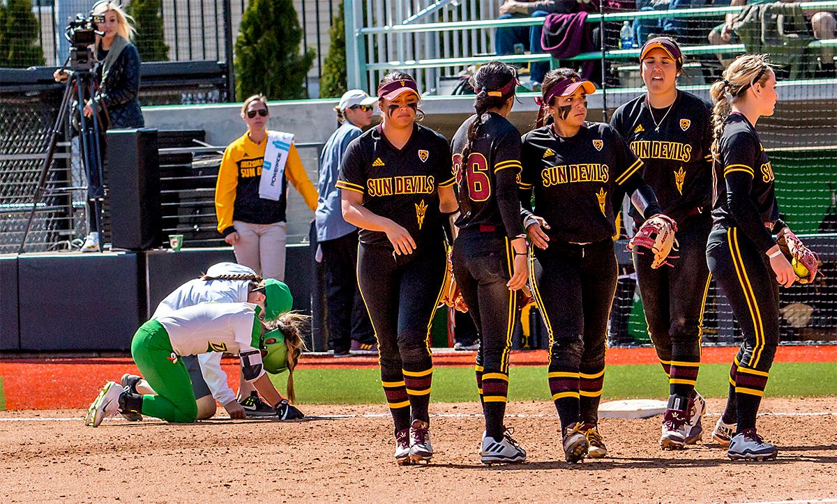 The Duck's Sammie Puentes (#5) receives help after colliding with a Sun Devils player on her run to first base. The Oregon Ducks Softball team took their third win over the Arizona Sun Devils, 1-0, in the final game of the weekends series that saw the game go into an eighth inning before the Duck?s Mia Camuso (#7) scored a hit allowing teammate Haley Cruse (#26) to run into home plate for a point. The Ducks are now 33-0 this season and will next play a double header against Portland State on Tuesday, April 4 at Jane Sanders Stadium. Photo by August Frank, Oregon News Lab