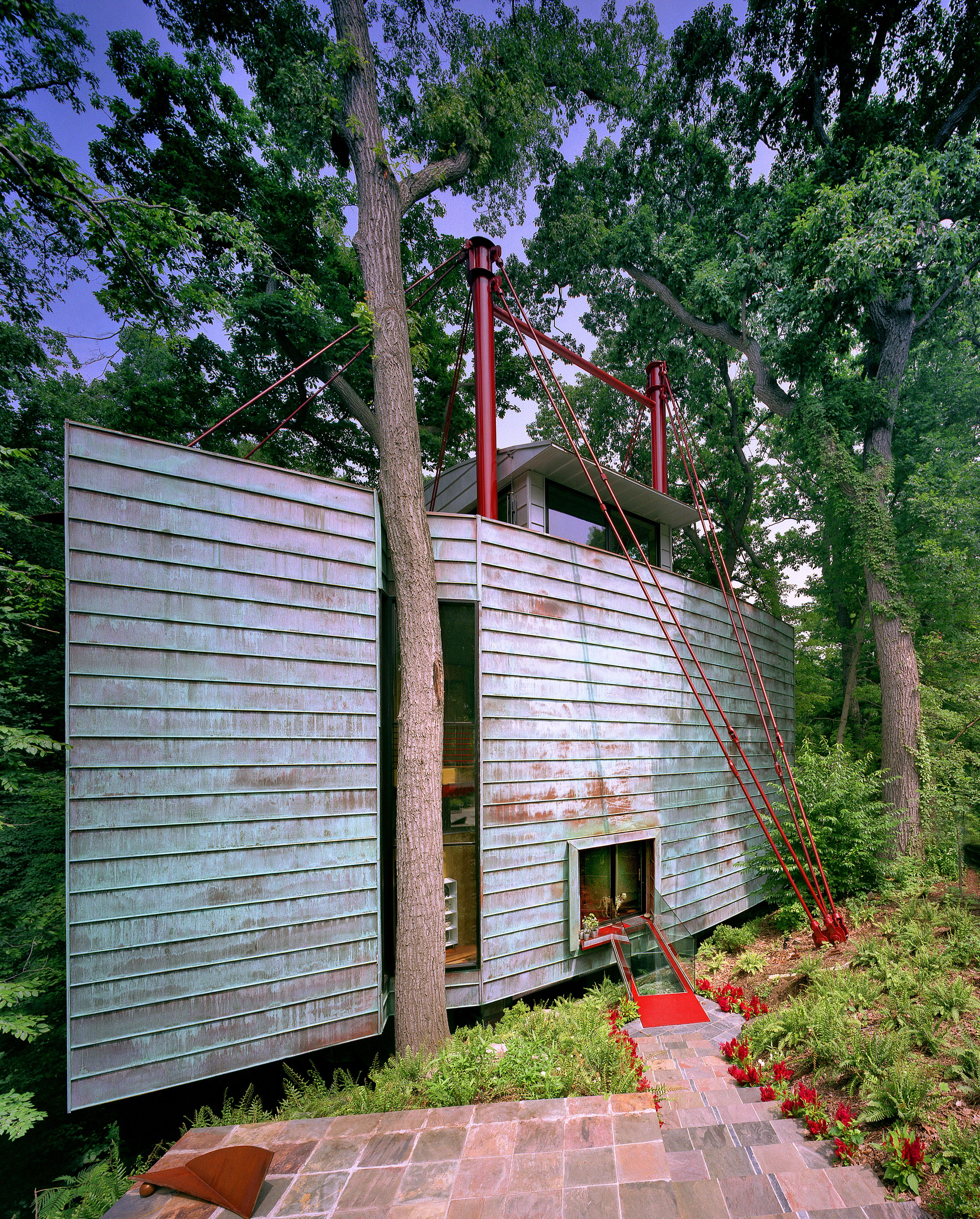 The home is inspired by the simple and natural virtues of the site's trees and rock outcroppings. An abundance of trees splitting rocks near a stream bed are the essences of the Park running through the center of D.C. The home is seen as an abstracted tree with a street side of patina copper planted on two columns at the cliff's edge hung by steel cables. The park side rear is clad with transparent super-insulated glazing. Trees are saved and wrap through the house. The design desires to blend into the park by its matching natural colors as well as its use of glass which reflectively display the preserved trees surrounding it. (Image: Ken Wyner)<p></p>