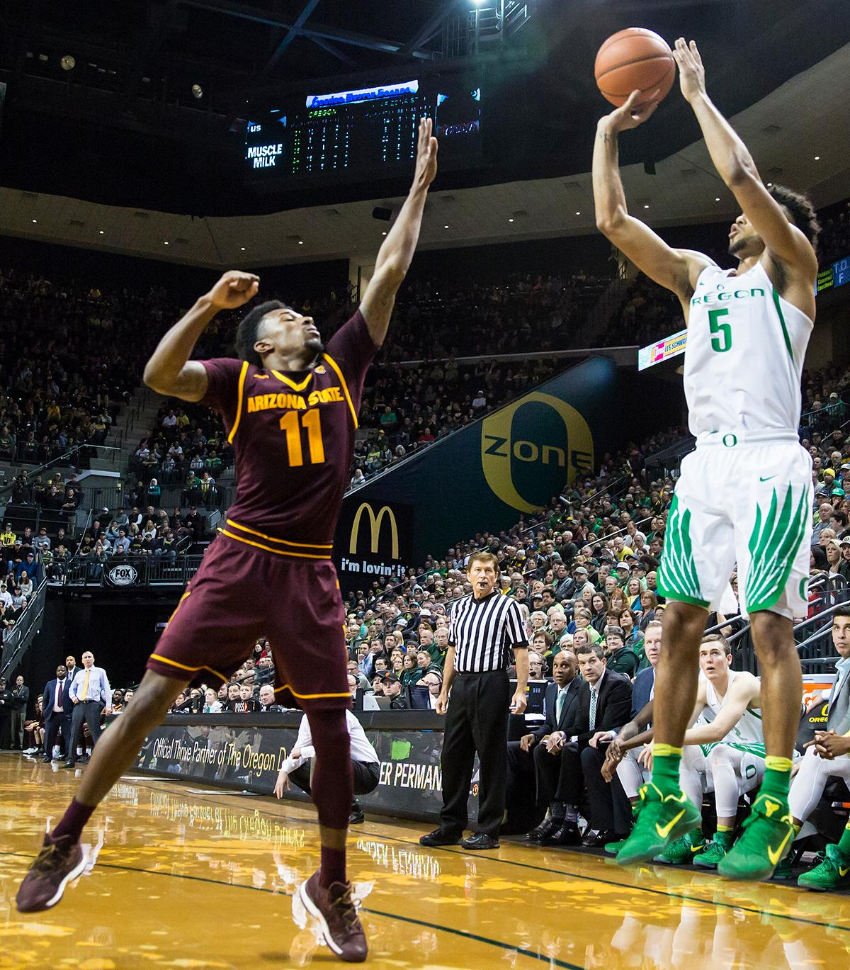Oregon guard Tyler Dorsey (#5) leaps to make a three-pointer over the outstretched arms of Arizona State guard Shannon Evans II (#11). Dorsey finished the night with 11 points. The Oregon Ducks defeated the Arizona State Sun Devils 71 to 70. Photo by Ben Lonergan, Oregon News Lab