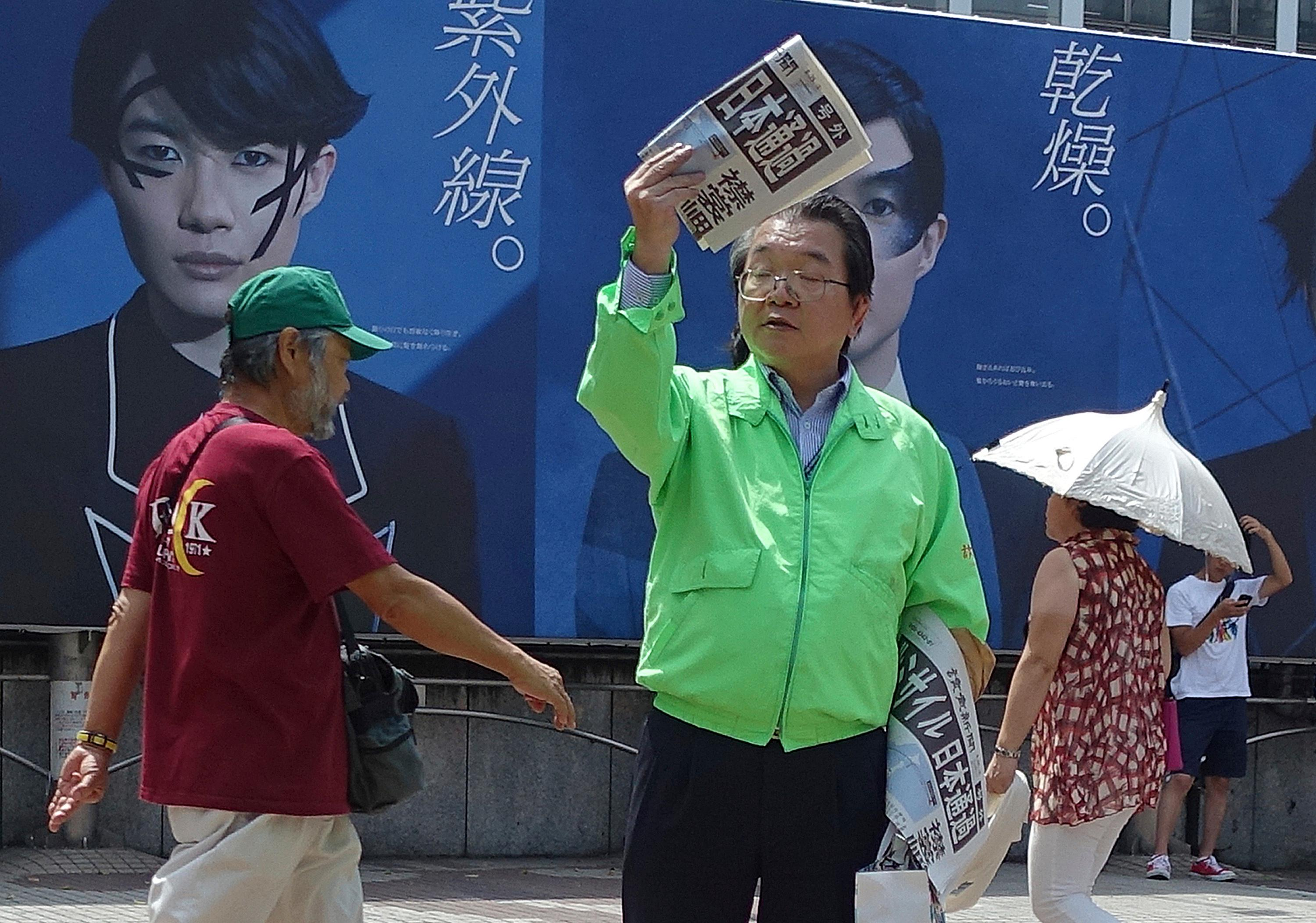 A staff of a Japanese newspaper hands out passer-by an extra newspaper reporting North Korea's rocket launch at a shopping street in Tokyo Tuesday, Aug. 29, 2017.  (AP Photo/Mari Yamaguchi)
