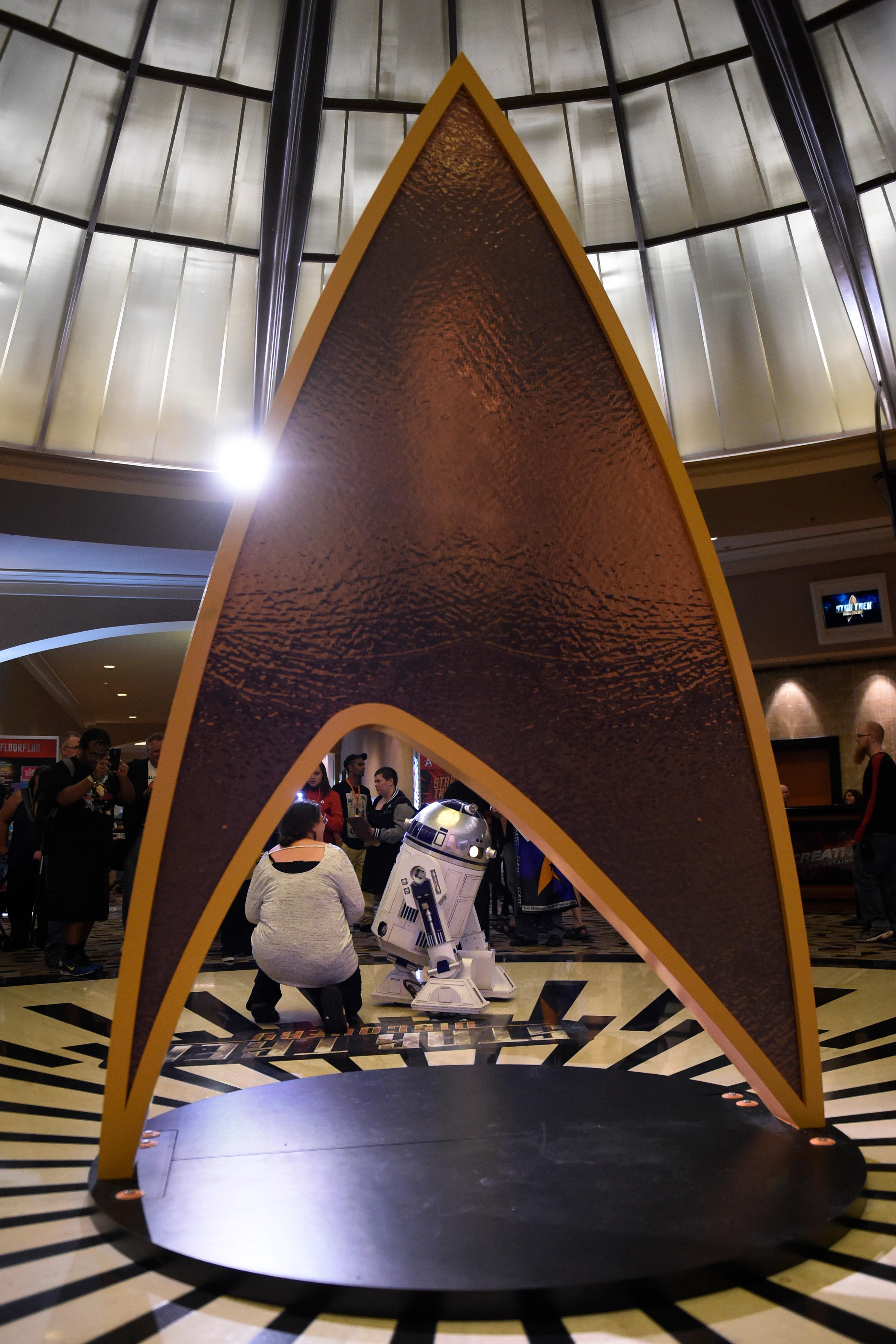 Attendees have their photo taken with a Star Wars R2D2 unit in front of a Star Trek Starfleet insignia during the 16th annual Las Vegas Star Trek Convention Saturday, August 5, 2017, at the Rio.  CREDIT: Sam Morris/Las Vegas News Bureau
