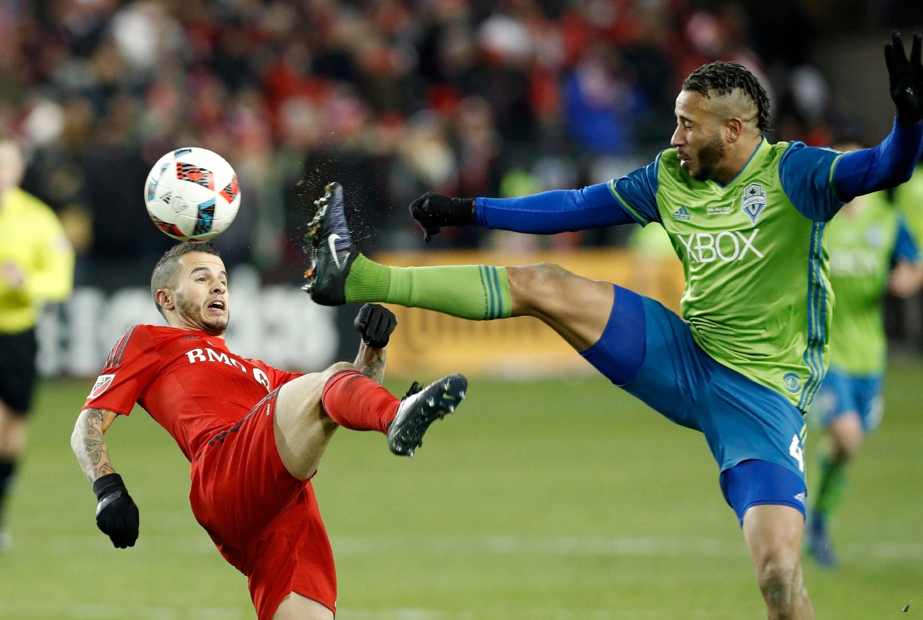 Seattle Sounders defender Tyrone Mears (4) clears the ball away from Toronto FC forward Sebastian Giovinco, left, during second-half MLS Cup final soccer action in Toronto, Saturday, Dec. 10, 2016. (Mark Blinch/The Canadian Press via AP)