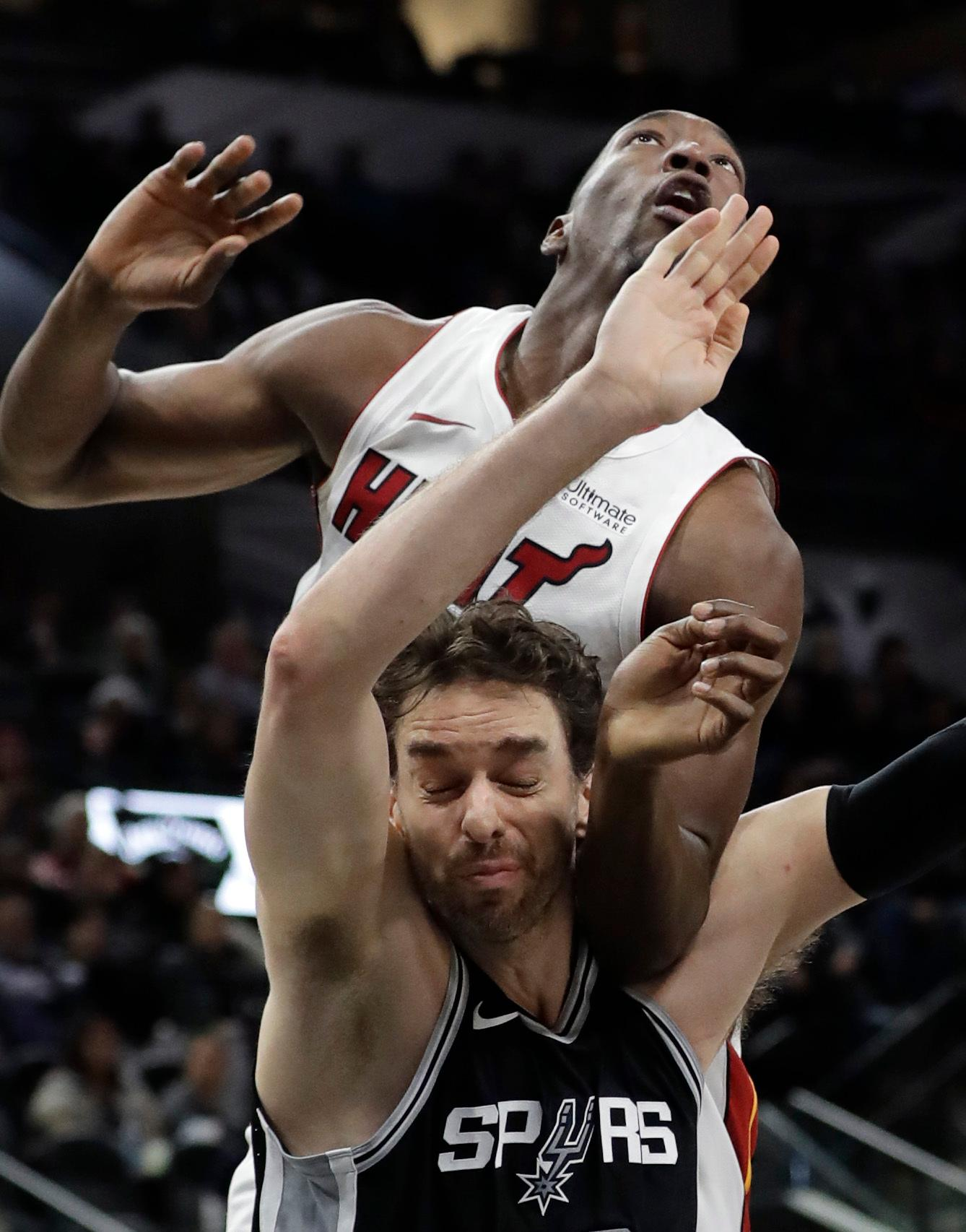 Miami Heat center Bam Adebayo, top, and San Antonio Spurs center Pau Gasol, bottom, jockey for position for a rebound during the first half of an NBA basketball game Wednesday, Dec. 6, 2017, in San Antonio. (AP Photo/Eric Gay)
