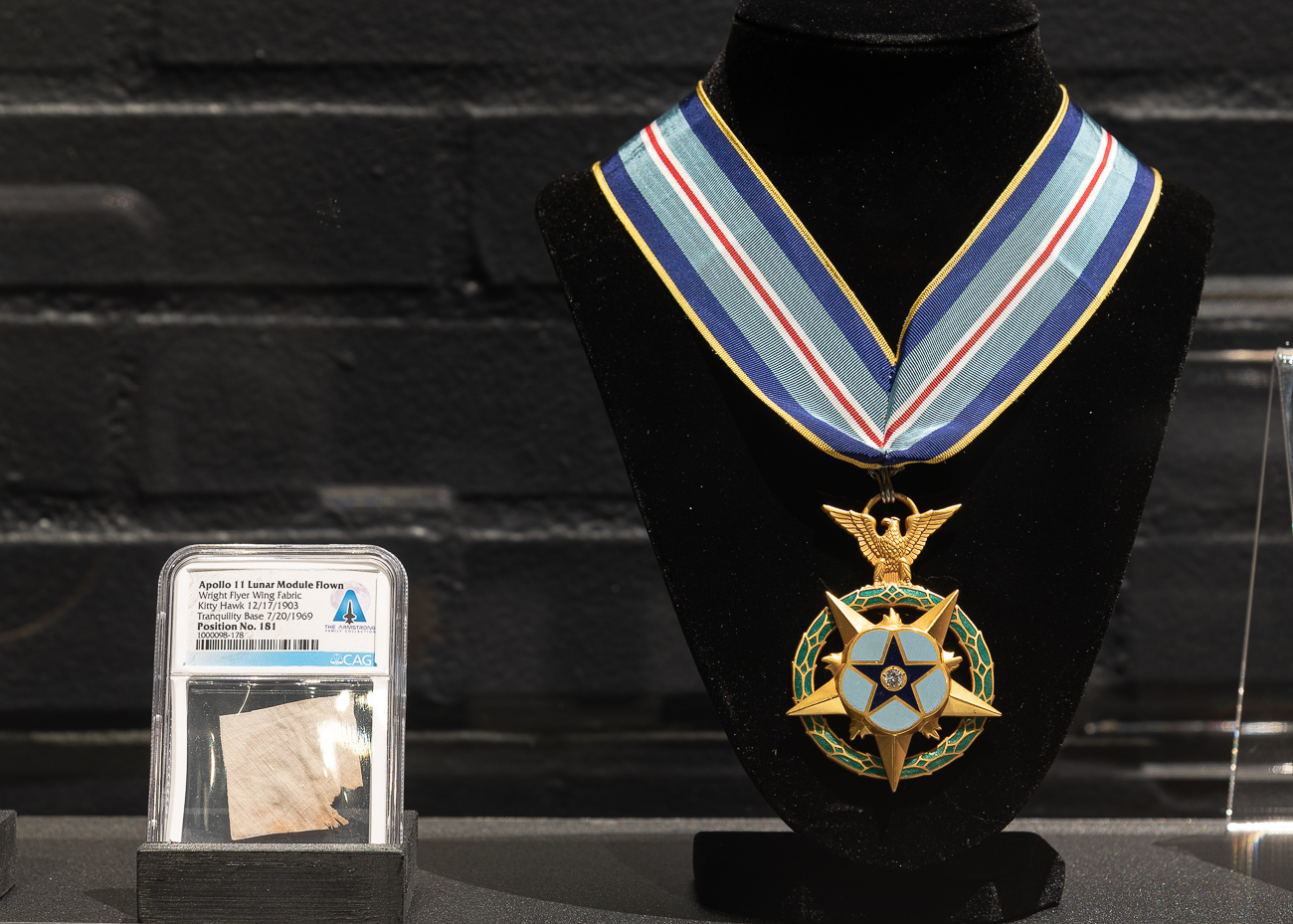 (LEFT) A piece of fabric from the Wright Flyer—the world's first airplane. It accompanied Neil Armstrong to the moon as a symbol of humankind's aerial achievement. (RIGHT) The Congressional Space Medal of Honor, awarded by President Jimmy Carter to Neil Armstrong. / Image: Phil Armstrong, Cincinnati Refined // Published: 10.2.19