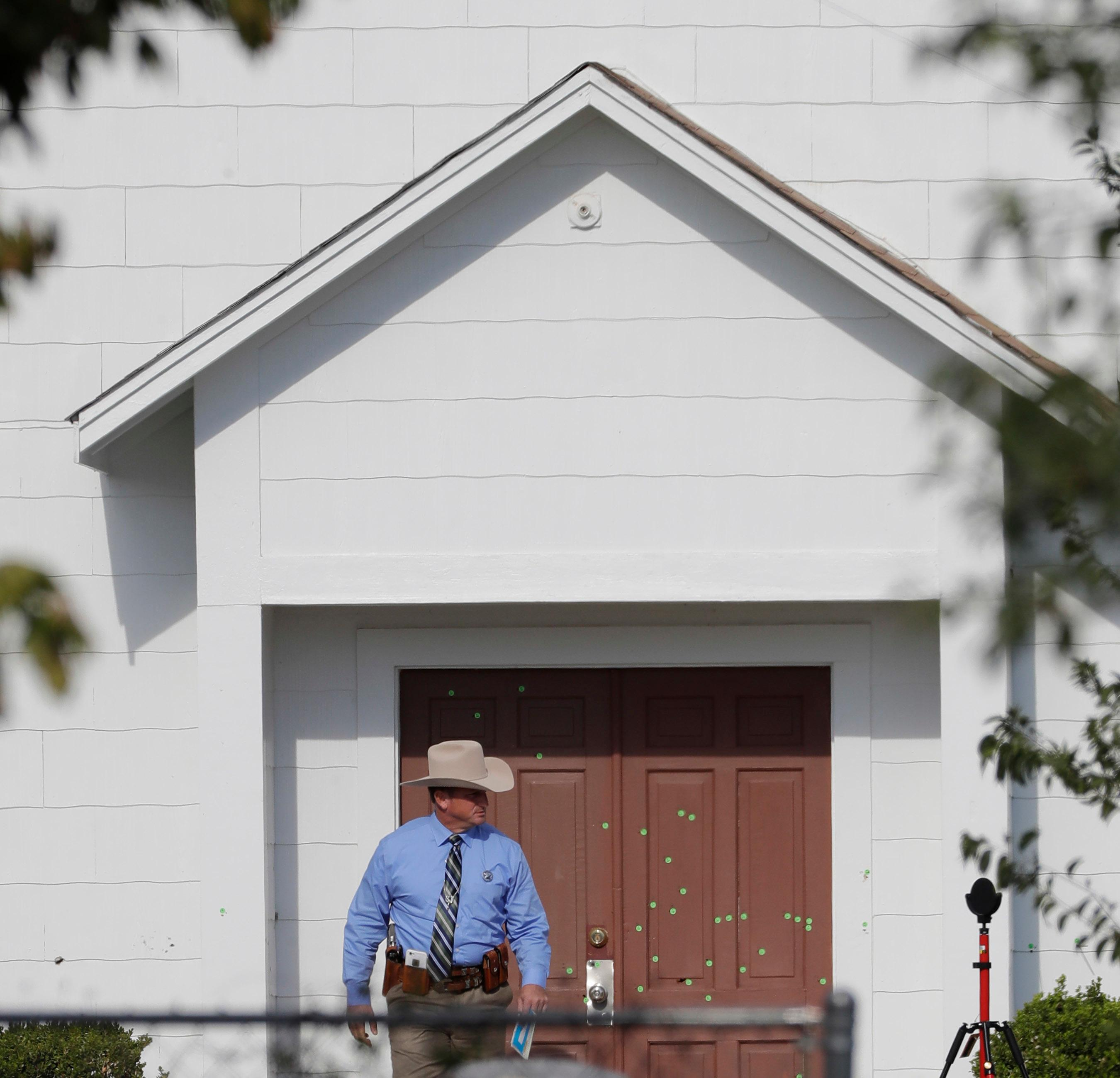 A law enforcement official leaves the First Baptist Church Tuesday, Nov. 7, 2017, in Sutherland Springs, Texas. A man opened fire inside the church in the small South Texas community on Sunday, killing more than two dozen and injuring others. (AP Photo/David J. Phillip)