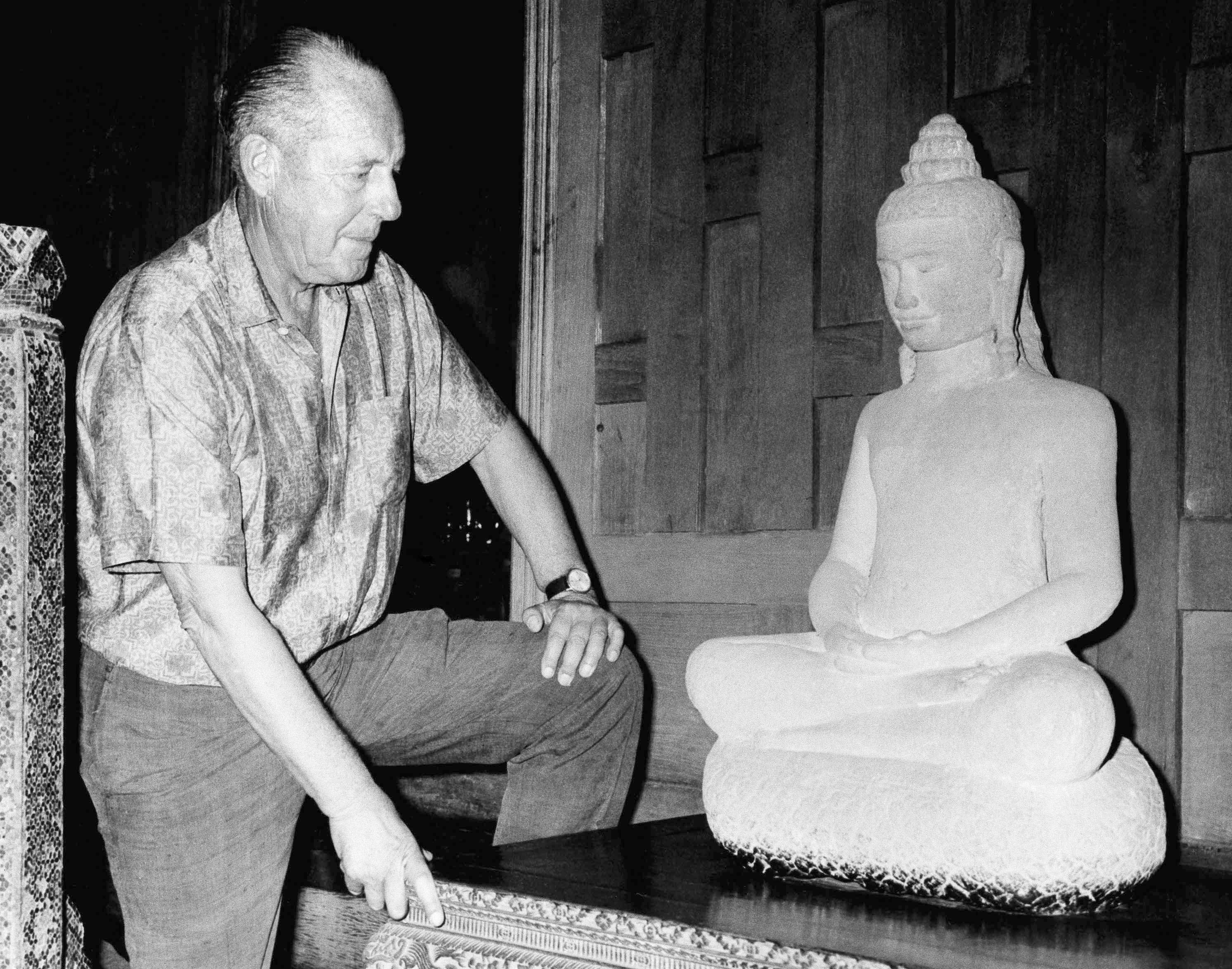 FILE - In this November 1966 file photo, American businessman Jim Thompson views a Buddha statue in Bangkok, Thailand. A new documentary is set to stir fresh debate over one of Asia's most enduring mysteries: What happened to Jim Thompson, Thailand's legendary silk king. (AP Photo/File)