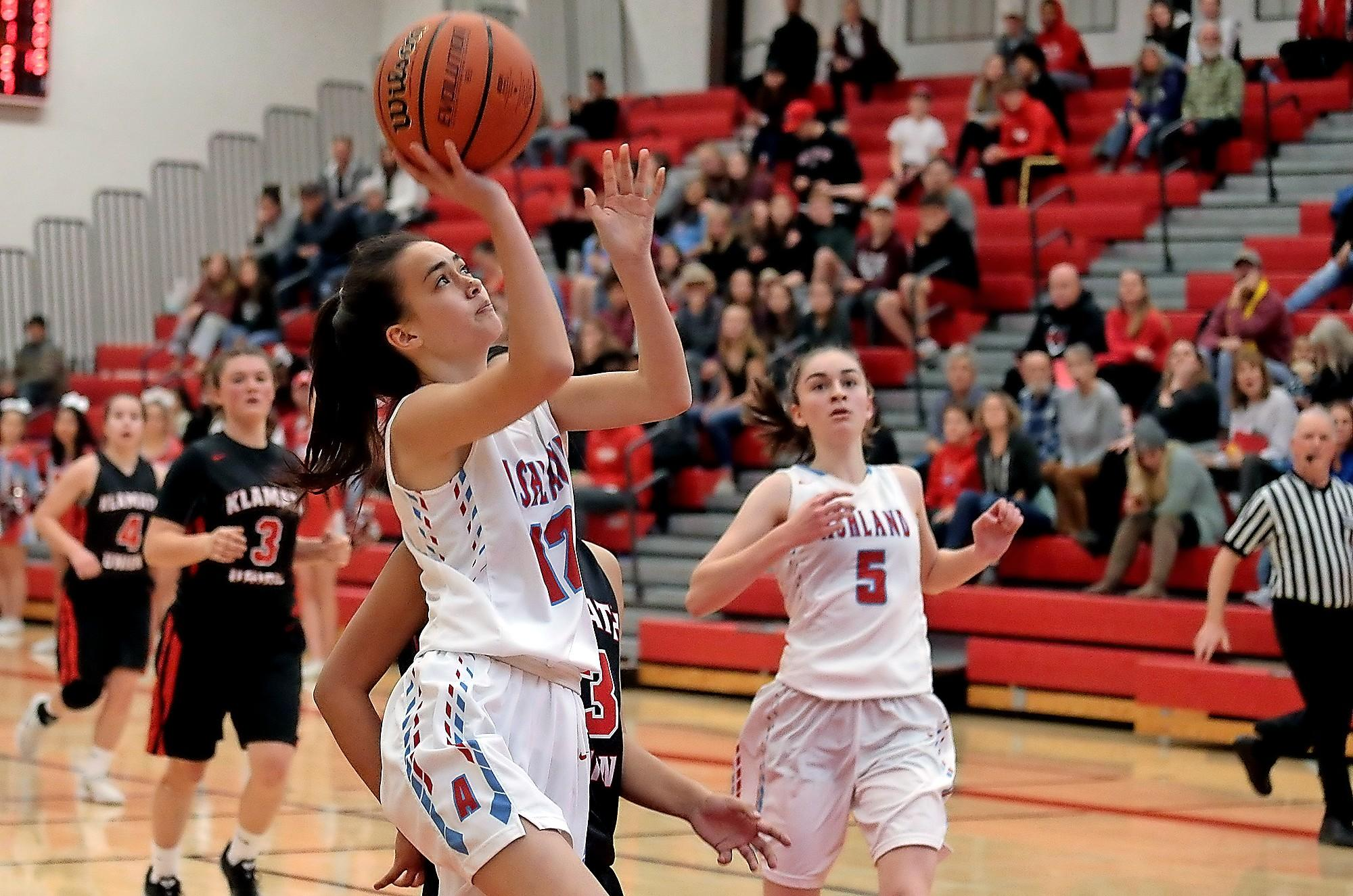 Ashland High junior Jackie Moran attempts to shoot past Klamath Union defenders, while teammate Jayd Sollinger looks on, at Mountain Avenue Gym on Wednesday.(PHOTO BY:  LARRY STAUTH JR)
