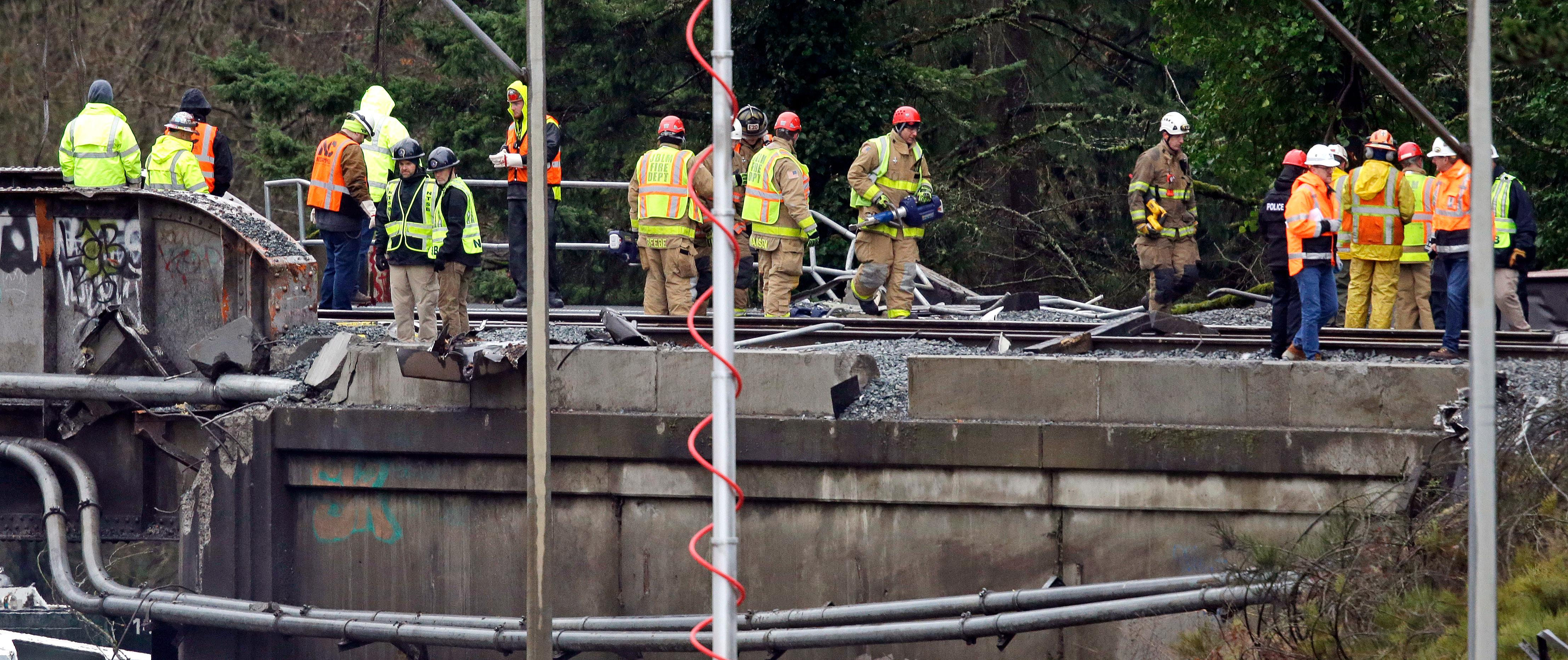 Workers stand atop a damaged railroad bridge at the scene of an Amtrak train crash onto Interstate 5 a day earlier Tuesday, Dec. 19, 2017, in DuPont, Wash. Federal investigators say they don't yet know why the Amtrak train was traveling 50 mph over the speed limit when it derailed Monday south of Seattle.  (AP Photo/Elaine Thompson)