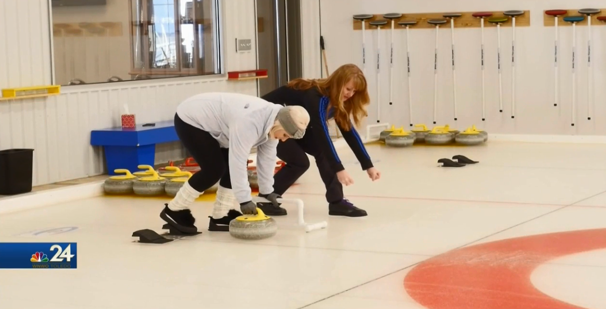 Black Swamp Curling instructor, Angie Jones, teaches Meteorologist Kimberly Newman how to push out of the hack (WNWO)<p></p>