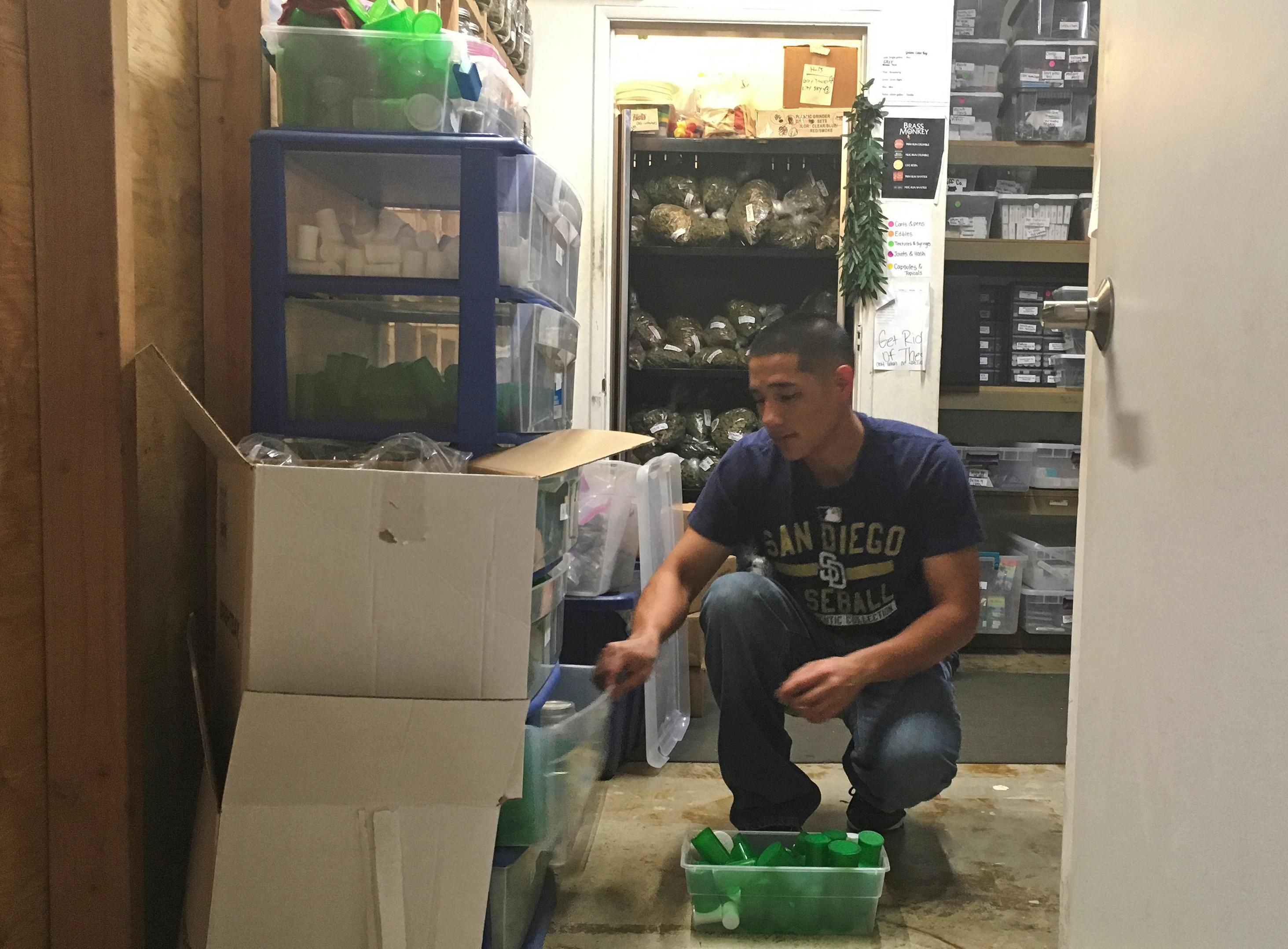In this Dec. 27, 2017 photo, Golden State Greens employee Alex Bradley loads product in the inventory room at the back office in San Diego, Calif. Dozens of California shops have cleared a final hurdle to sell marijuana for recreational use starting Monday, Jan. 1, 2018, and regulators will work through the weekend to grant more licenses. (AP Photo/Elliot Spagat)
