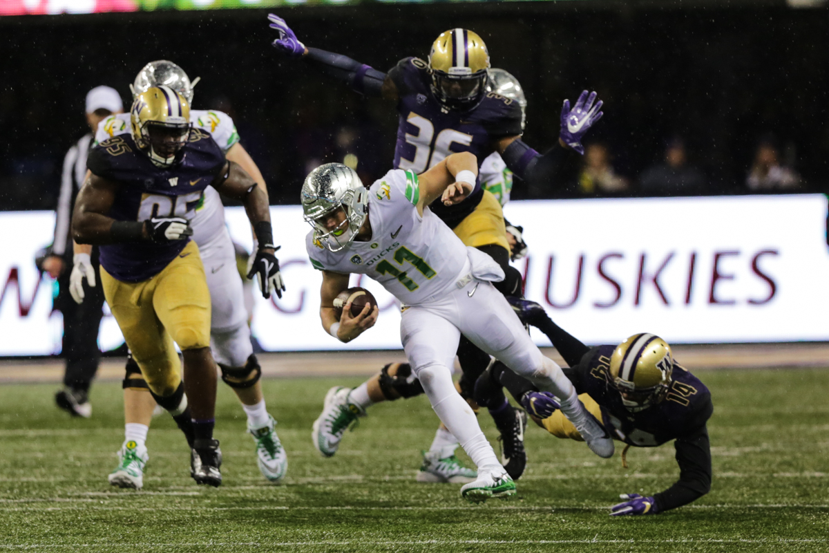 Oregon quarterback Braxton Burmeister (#11) is dragged down by his ankle by Washington defensive back Jojo McIntosh (#14). The Oregon Ducks fell to the Washington Huskies 38 - 3 on a cold and rainy night in Seattle, Washington.  Oregon opened the game with a field goal on their first drive and was held scoreless from then on.  Photo by Austin Hicks, Oregon News Lab