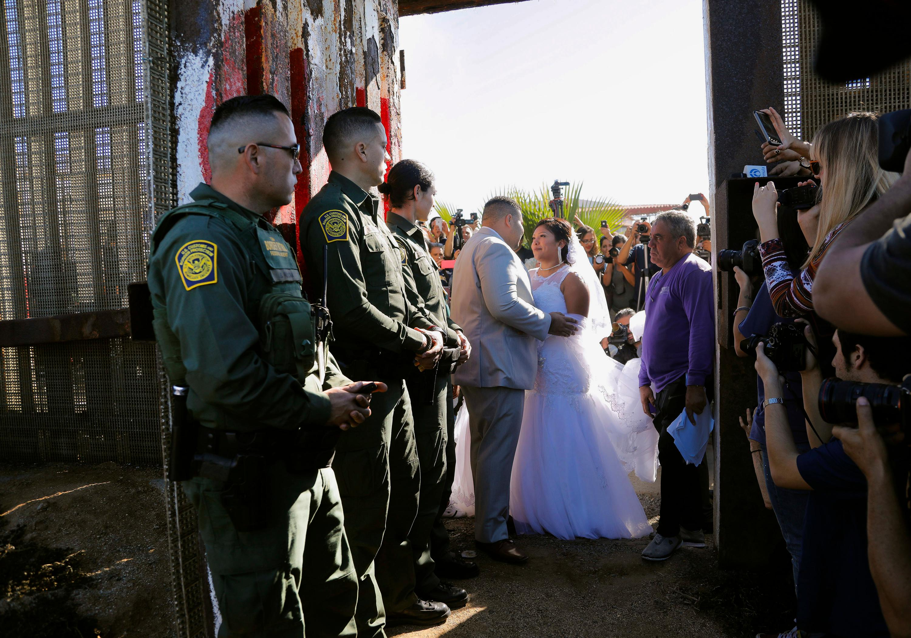 "In this Saturday, Nov. 18, 2017, photo, Brian Houston, of Rancho San Diego, center left, and Evelia Reyes, right, of Tijuana, Mexico, look at each other in their wedding at the ""Door of Hope,"" part of the border fence between the U.S. and Mexico. The United States man and the Mexican woman wedded Saturday between the doors of a steel border gate that opens for only an hour or so every year. Their wedding in San Diego was the first for an opening of the gate known as the Door of Hope. (Howard Lipin//The San Diego Union-Tribune via AP)"